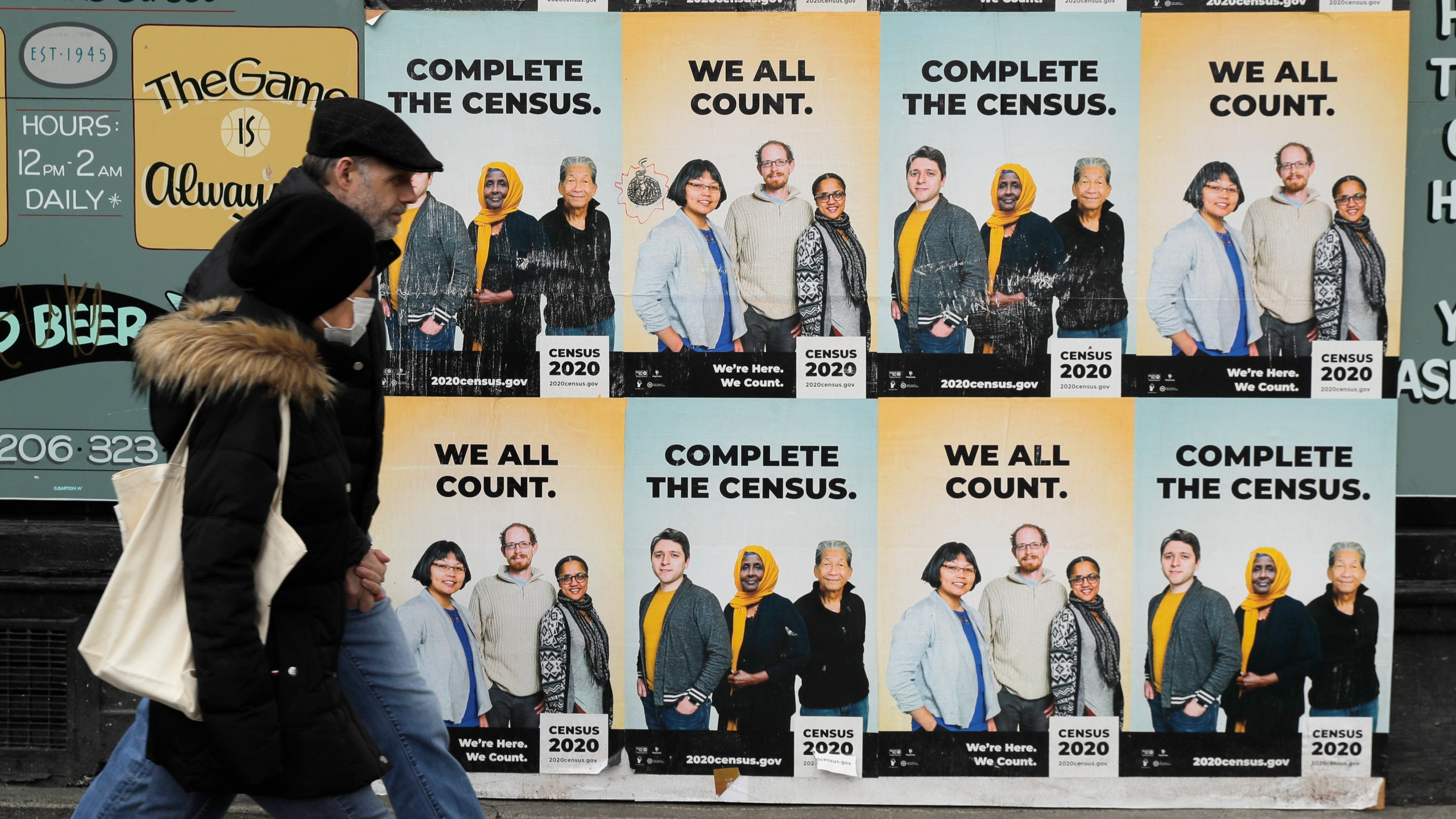 In this Wednesday, April 1, 2020 file photo, People walk past posters encouraging participation in the 2020 Census in Seattle's Capitol Hill neighborhood. From McKenzie County, North Dakota to St. Johns County Florida, the growth in the number of people who identified as multiracial on 2020 census responses soared over the last decade, rising from under 3% to more than 10% of the U.S. population from 2010 and 2020.(AP Photo/Ted S. Warren, File)