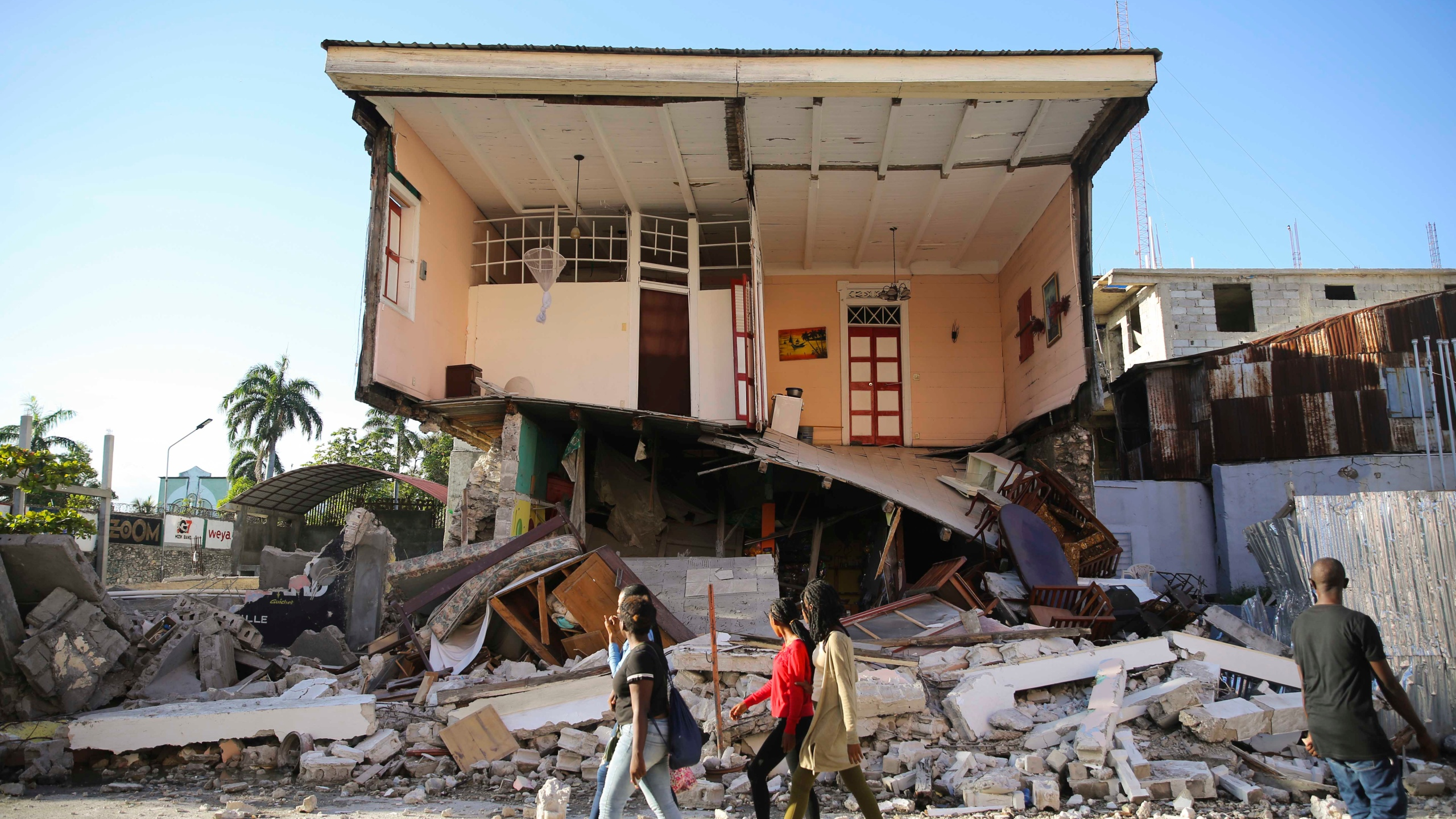 People walk past a home destroyed by the earthquake in Les Cayes, Haiti, Saturday, Aug. 14, 2021. A 7.2 magnitude earthquake struck Haiti on Saturday, with the epicenter about 125 kilometers (78 miles) west of the capital of Port- au-Prince, the US Geological Survey said. (AP Photo/Joseph Odelyn)