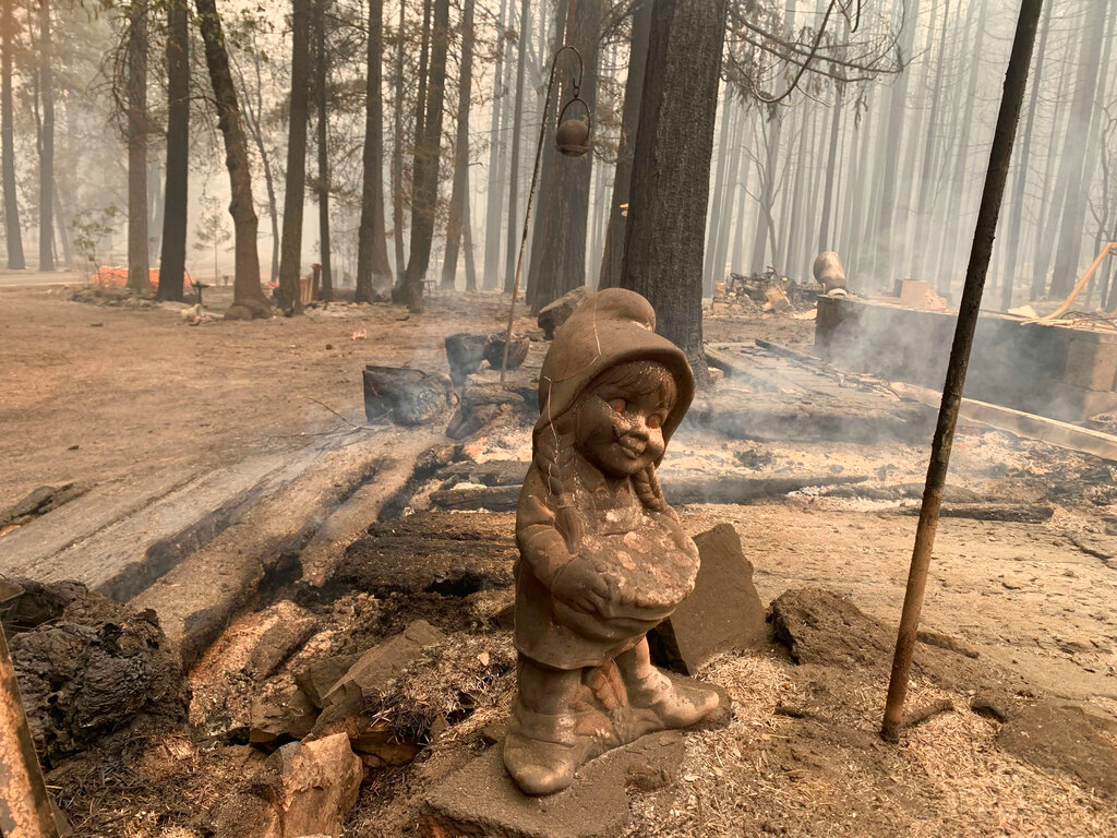 A surviving ceramic statue is seen outside a house that burned along North Arm Road in Plumas County near Taylorsville, Calif., Sunday, Aug. 15, 2021. (AP Photo/Eugene Garcia)