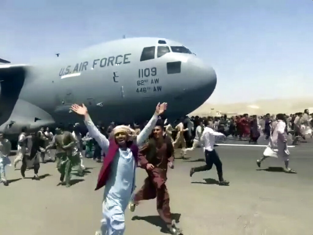 Hundreds of people run alongside a U.S. Air Force C-17 transport plane as it moves down a runway of the international airport, in Kabul, Afghanistan on Aug.16. 2021. Thousands of Afghans have rushed onto the tarmac of Kabul's international airport, some so desperate to escape the Taliban capture of their country that they held onto an American military jet as it took off and plunged to death. (Verified UGC via AP)