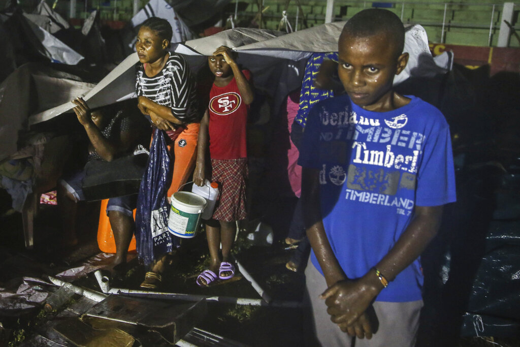 People affected by the Saturday's earthquake take cover from the rain of Tropical Depression Grace at a refugee camp in Les Cayes, Haiti, Monday, Aug. 16, 2021. (AP Photo/Joseph Odelyn)