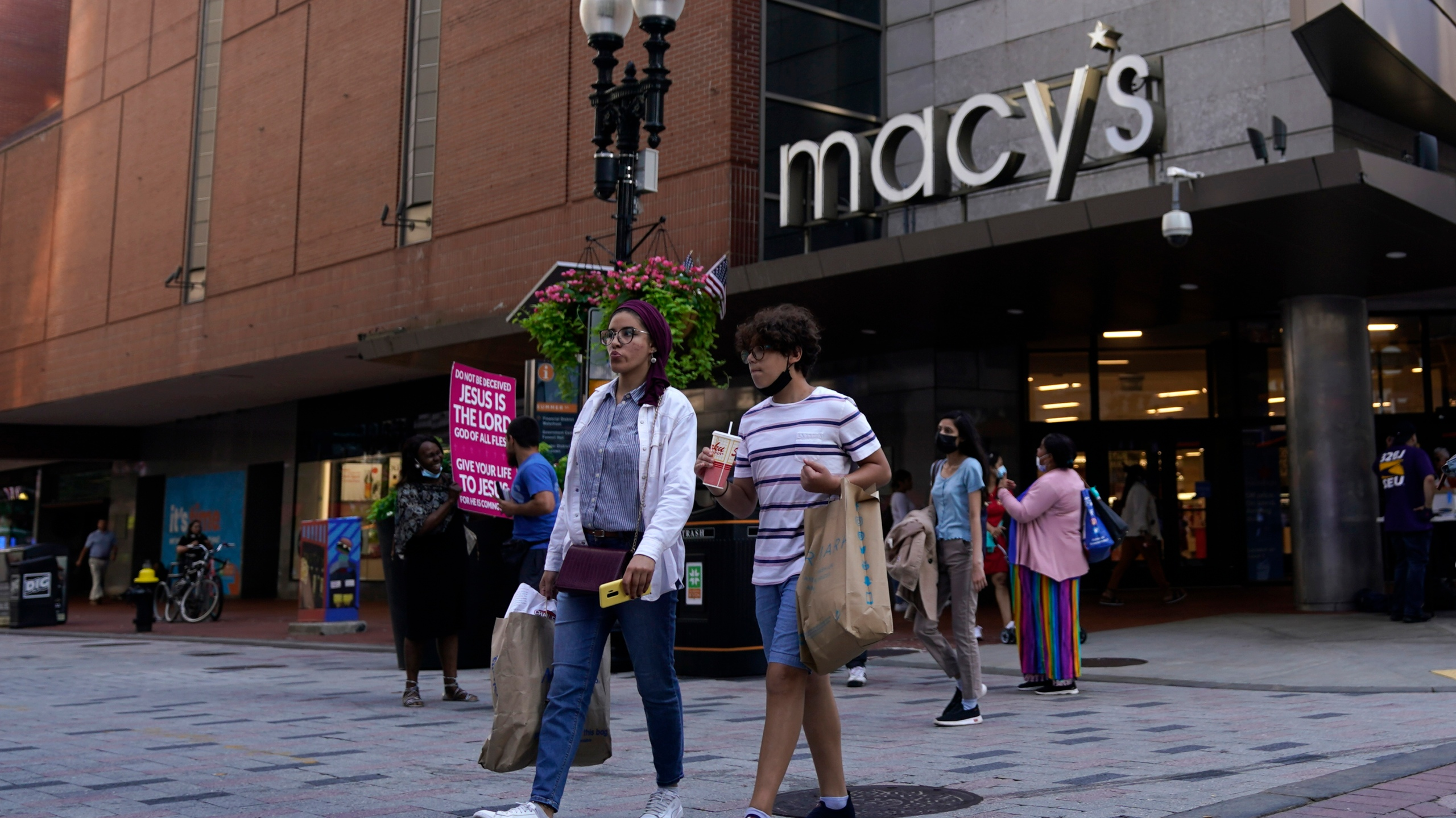 In this July 14, 2021 file photo, pedestrians pass the Macy's store in the Downtown Crossing shopping area, in Boston. (AP Photo/Charles Krupa, File)