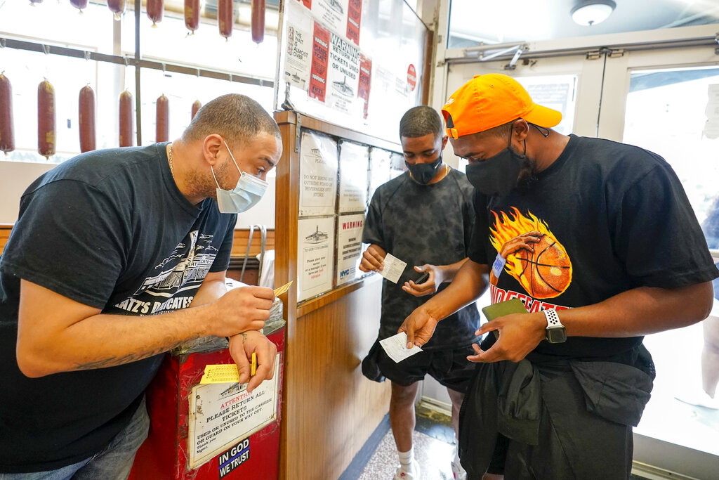 A Katz's Deli employee, left, checks the proof of vaccination from customers who will be eating inside the restaurant, Tuesday, Aug. 17, 2021, in New York. (AP Photo/Mary Altaffer)