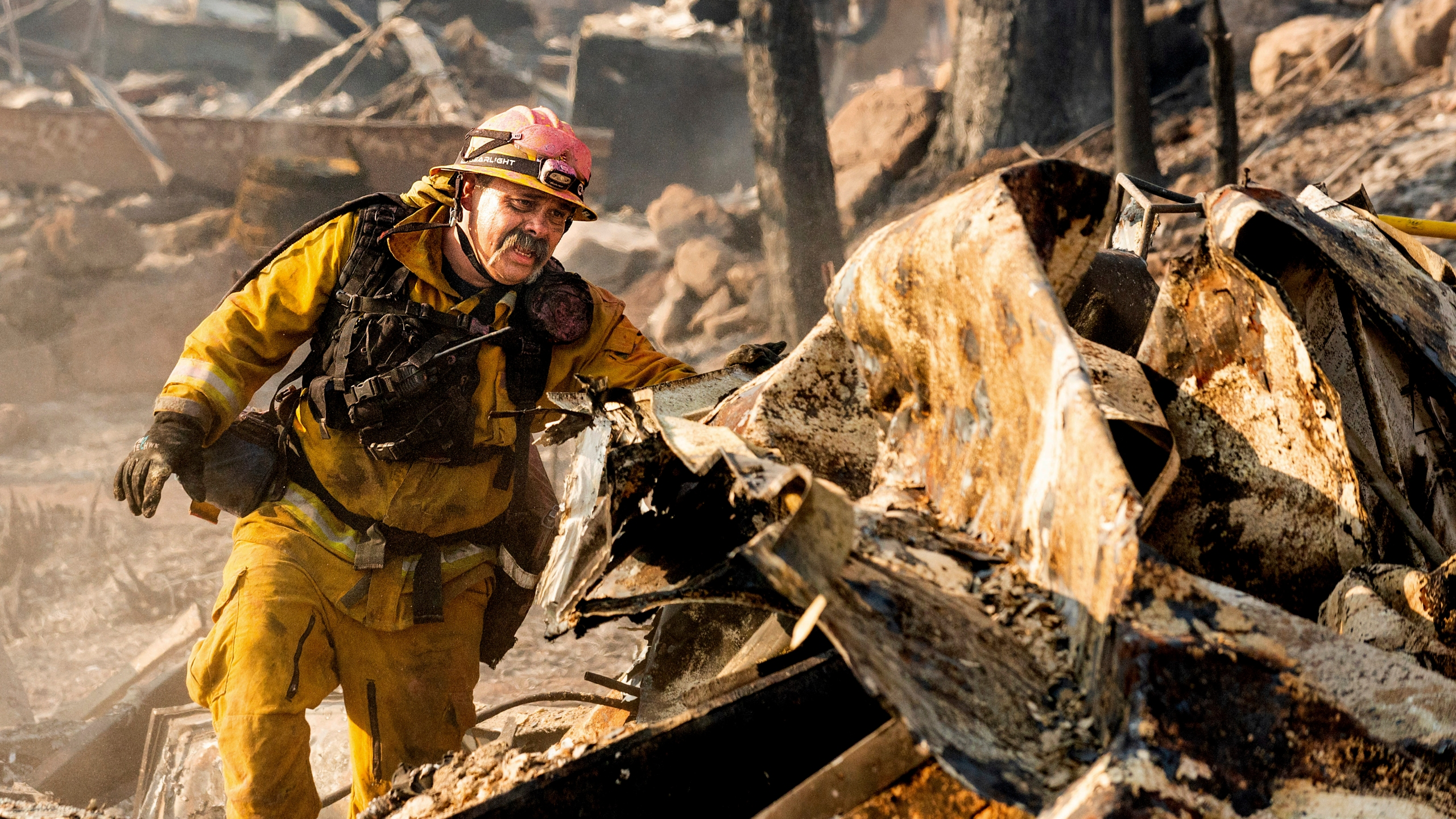 Firefighter Jesse Viescas searches through a residence at Cache Creek Mobile Home Estates where the Cache Fire leveled dozens of homes, Wednesday, Aug. 18, 2021, in Clearlake, Calif. (AP Photo/Noah Berger)