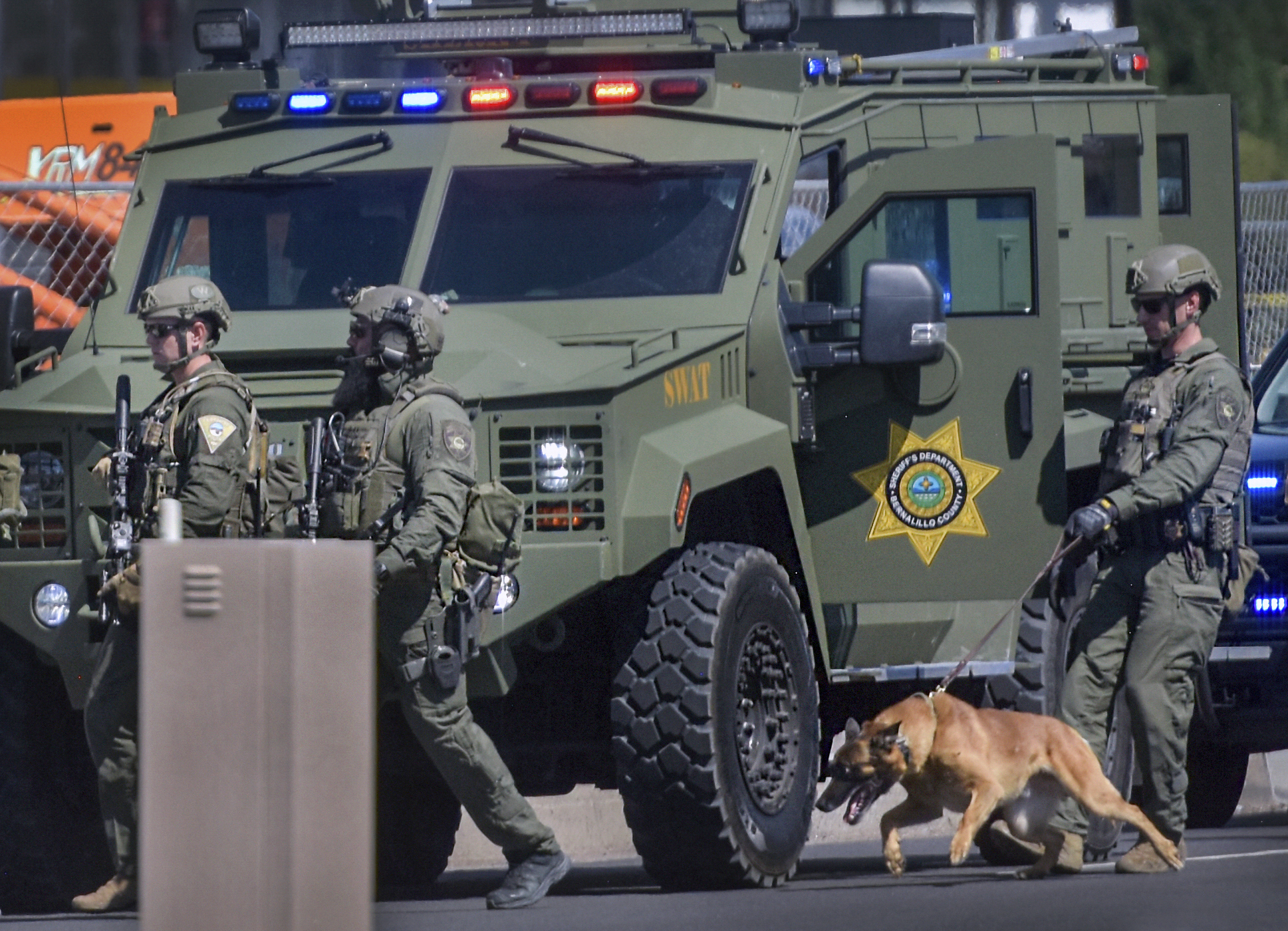 Tactical officers search for a suspect after a shootout that left multiple officers injured in northeast Albuquerque, N.M. on Thursday, Aug. 19, 2021. (Robert Browman/The Albuquerque Journal via AP)