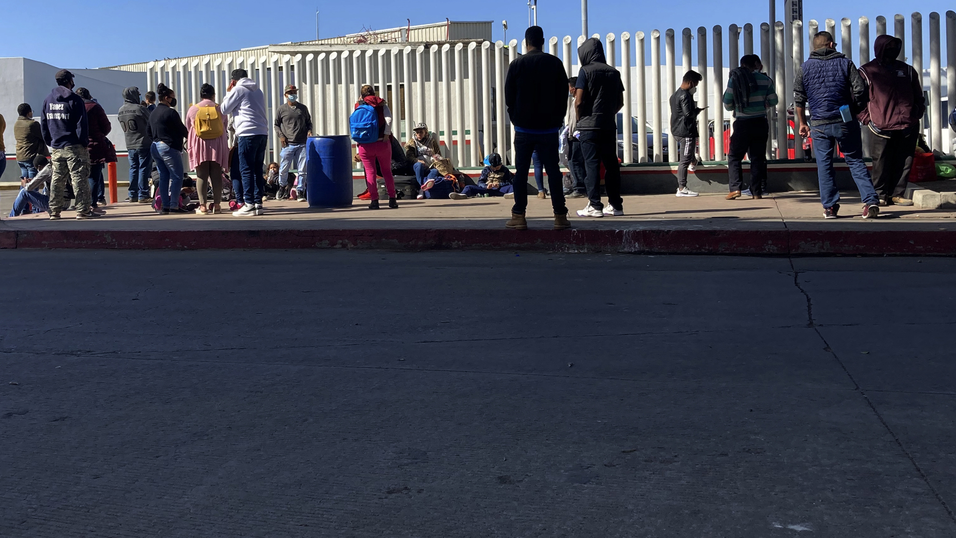 Migrants waiting to cross into the United States wait for news at the border crossing in Tijuana on Feb. 17, 2021.(Elliot Spagat/Associated Press)