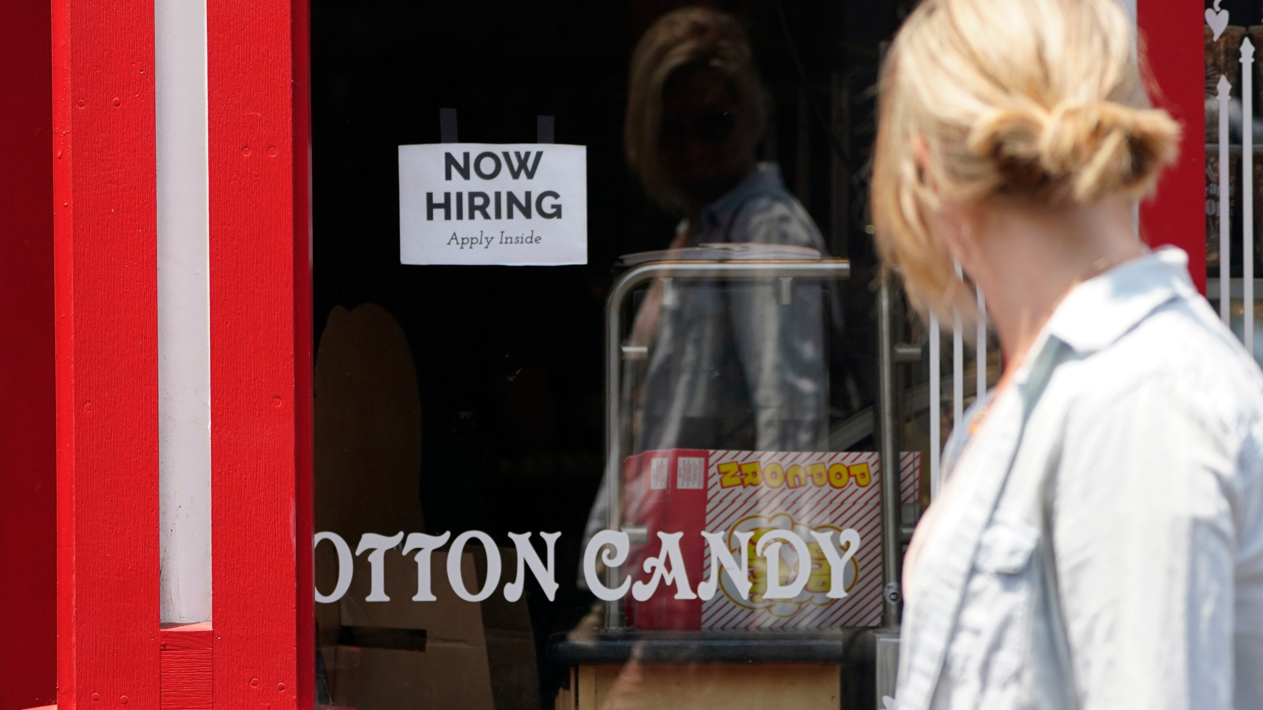 """A """"NOW HIRING"""" sign is posted in the window of The Wharf Chocolate Factory at Fisherman's Wharf in Monterey on Aug. 6, 2021. (Rich Pedroncelli / Associated Press)"""
