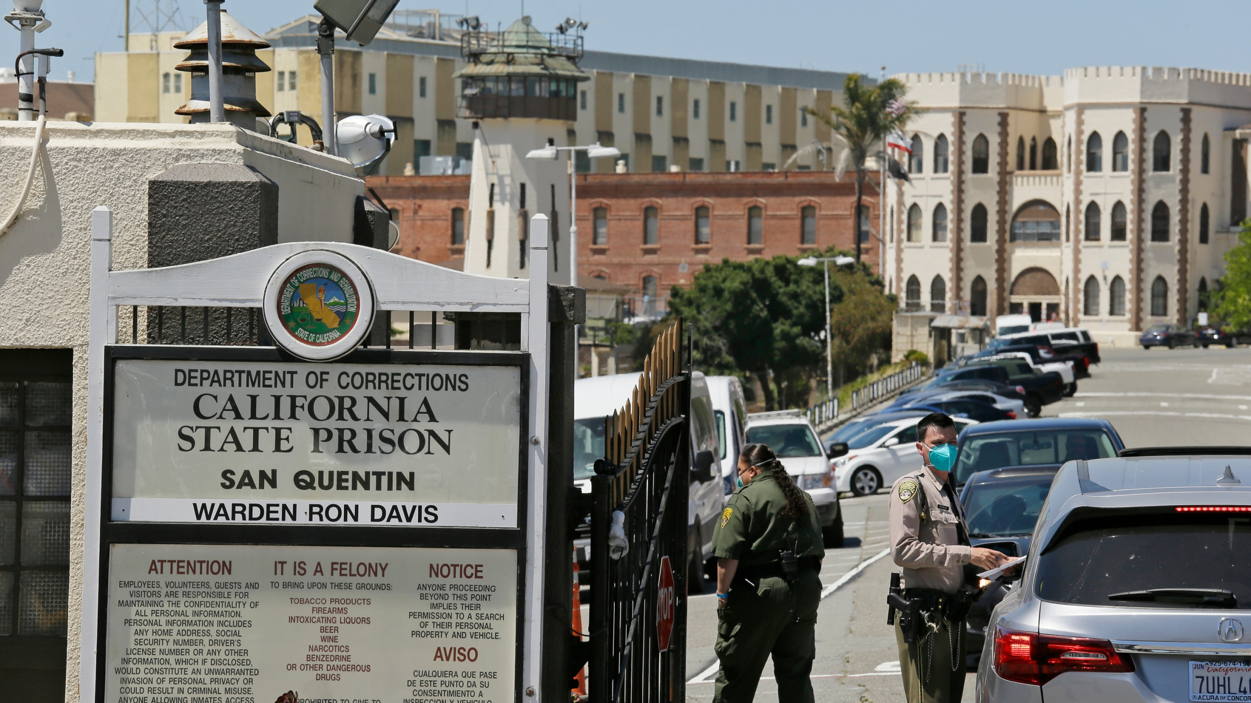 In this July 9, 2020 file photo a correctional officer checks a car entering the main gate of San Quentin State Prison, in San Quentin, Calif. California is mandating that some correctional officers at state and local facilities and detention centers to get vaccinated unless they qualify for a religious or medical exemption. (AP Photo/Eric Risberg,File)