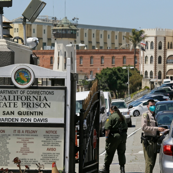 In this July 9, 2020 file photo a correctional officer checks a car entering the main gate of San Quentin State Prison, in San Quentin, Calif. (AP Photo/Eric Risberg,File)