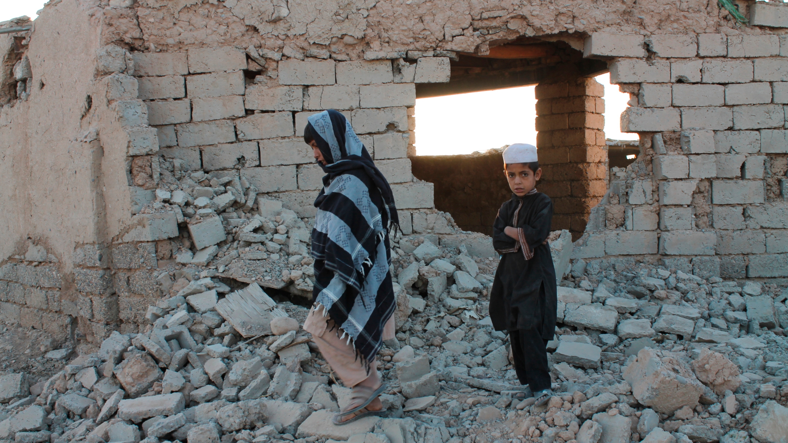 Afghan boys walk near a damaged house after airstrikes in two weeks ago during a fight between government forces and the Taliban in Lashkar Gah, Helmand province, southwestern, Afghanistan, Saturday, Aug. 21, 2021. (AP Photo/Abdul Khaliq)