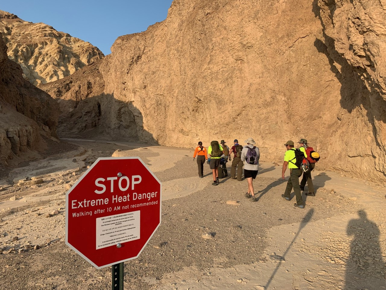 """In this Wednesday, Aug. 18, 2021, photo provided by the National Park Service, an inter-agency search and rescue crew walks past a sign reading"""" """"Stop, Extreme Heat Danger,"""" with park rangers responding on foot near Red Cathedral along the Golden Canyon Trail in Death Valley National Park, Calif. (National Park Service via AP)"""