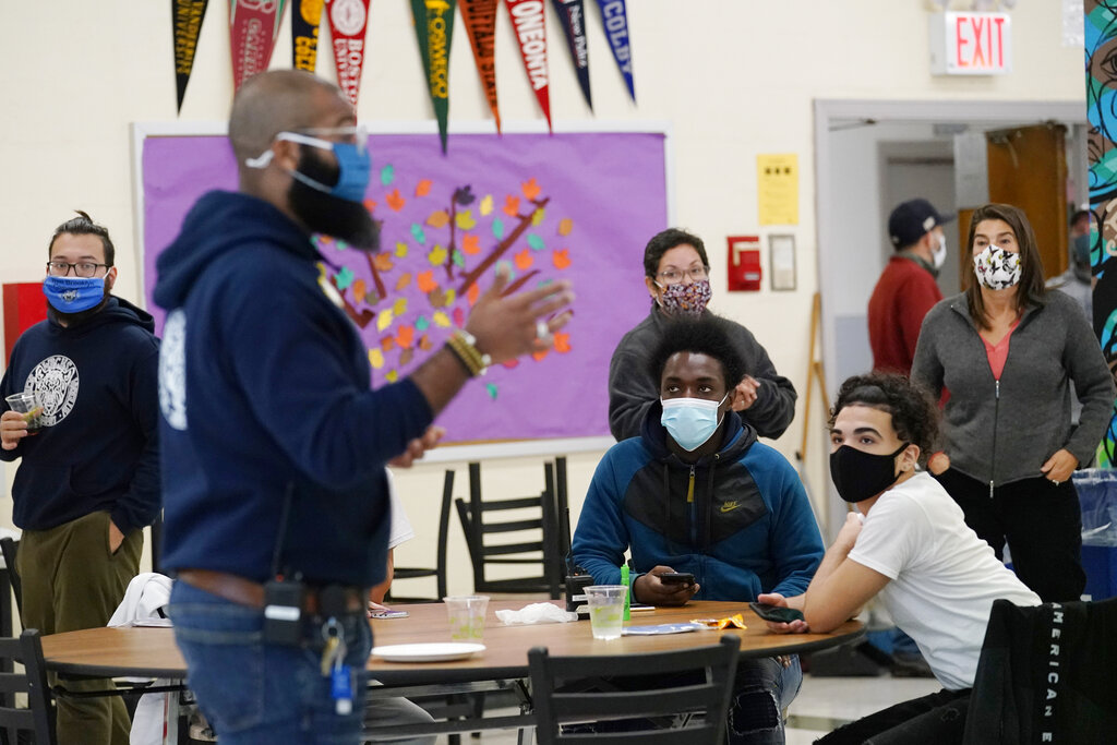 In this Oct. 29, 2020, file photo, students, teachers, administrators and counselors listen as principal Malik Lewis, second from left, teaches them a history lesson at West Brooklyn Community High School in New York. (AP Photo/Kathy Willens, File)