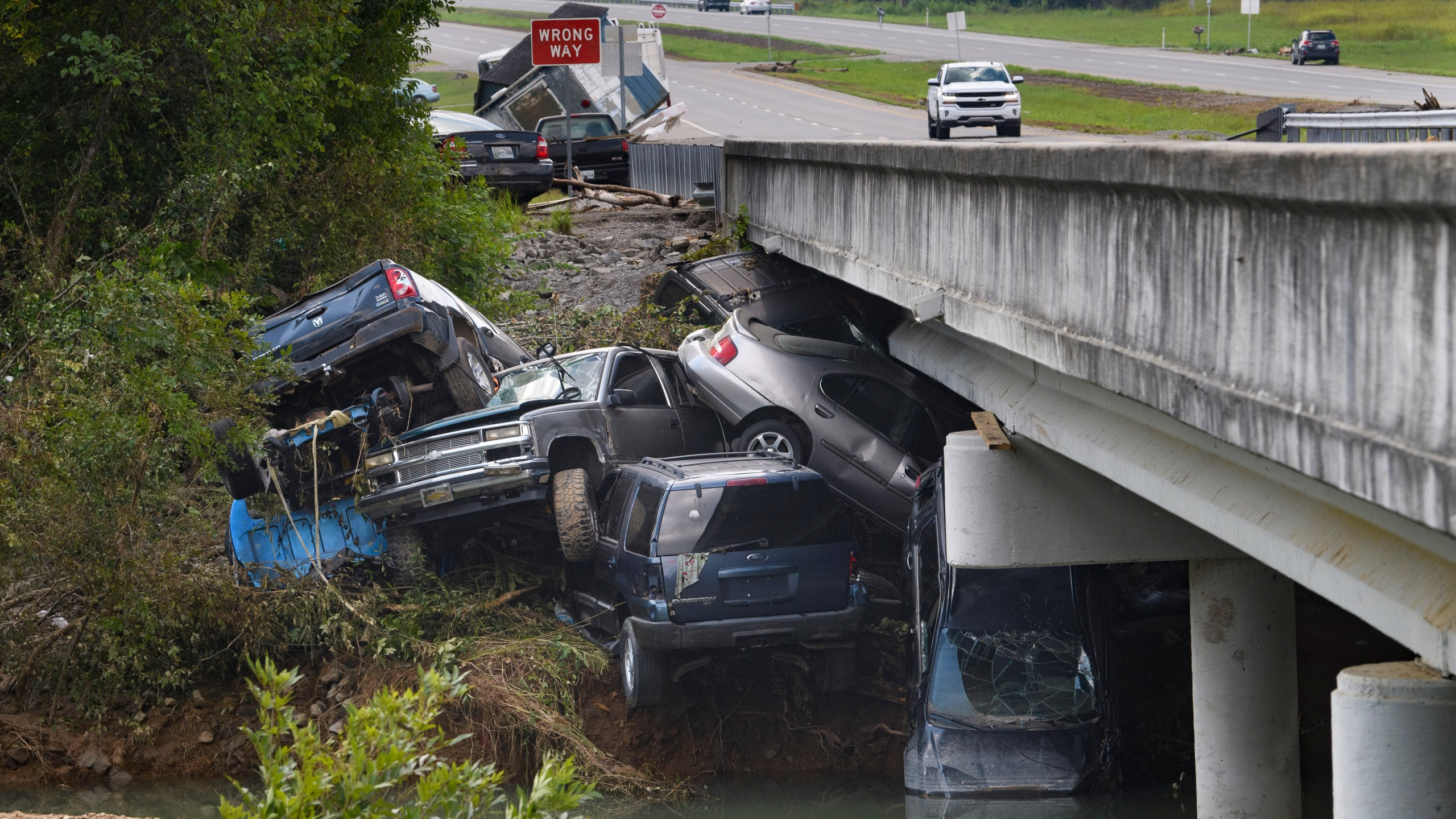 Cars are stacked on top of each other on the banks of Blue Creek being swept up in flood water on Aug. 23, 2021, in Waverly, Tenn. (John Amis/Associated Press)