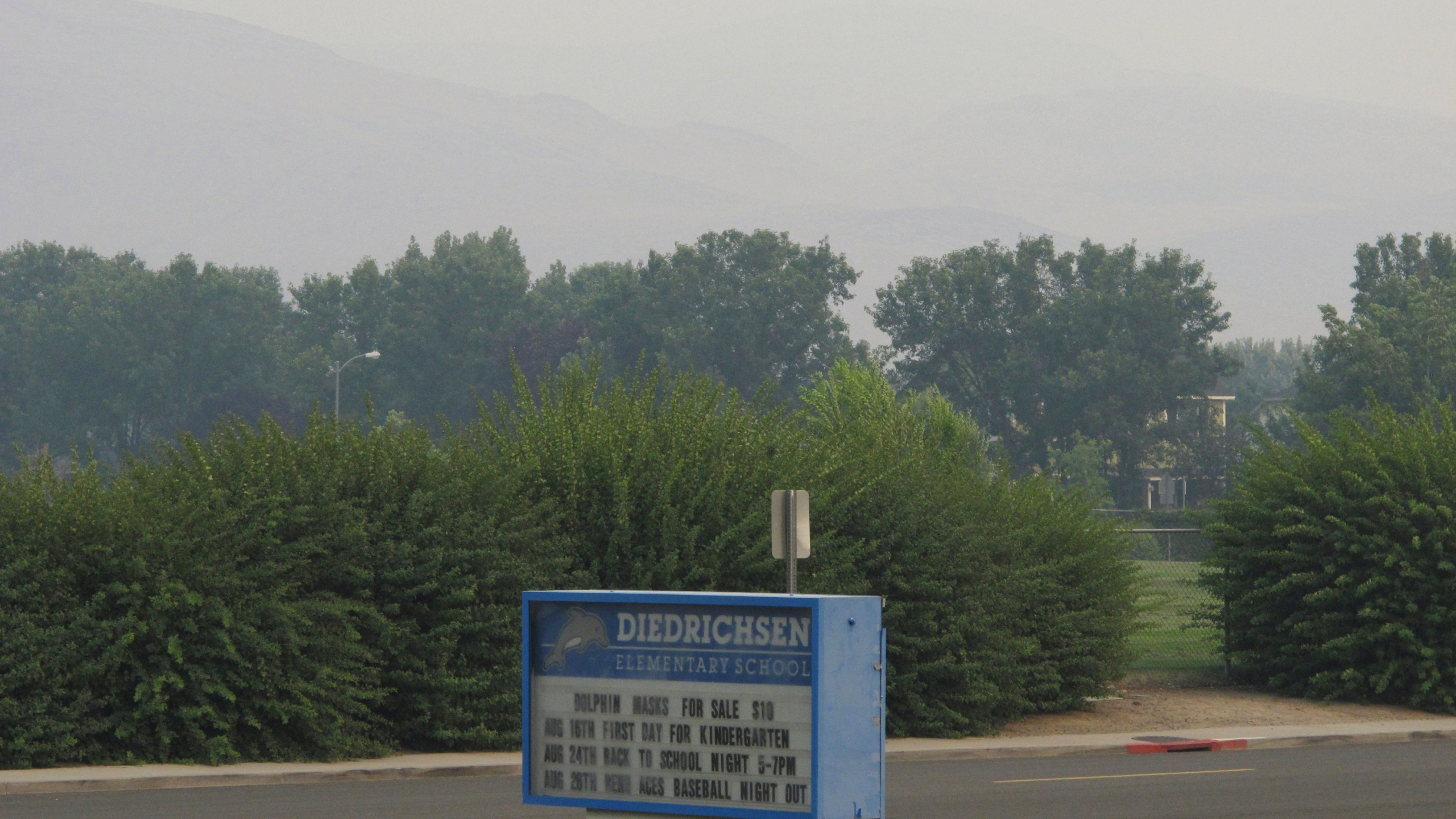 """Smoke from wildfires in California obscures the Pah Hah Range, Monday, Aug. 23, 2021, about 1 mile east of Diedrichsen Elementary School in Sparks, Nev., which was closed due to hazardous air quality. The Washoe County School District closed all schools including in Reno, Sparks and parts of Lake Tahoe on Monday due to the health hazard. The county health district also urged the general public to """"stay inside as much as possible"""" due to conditions expected to continue through Wednesday. (AP Photo/Scott Sonner)"""