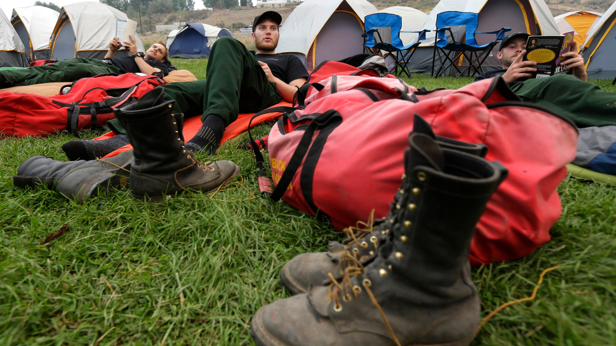 In this Aug. 25, 2015, file photo, Mac Mega, center, rests with fellow firefighters from Oregon-based Grayback Forestery, at a camp for firefighters battling the Okanogan Complex Fire in Okanogan, Wash. Empty cow pastures on one day can be bustling with hundreds of firefighters the next as fire camps with colorful tent cities spring up. Truckloads of supplies and equipment are needed to keep wildland firefighters effective at fighting flames for weeks on end. The size of each camp is determined by the size and complexity of the wildfire. (AP Photo/Ted S. Warren, File)