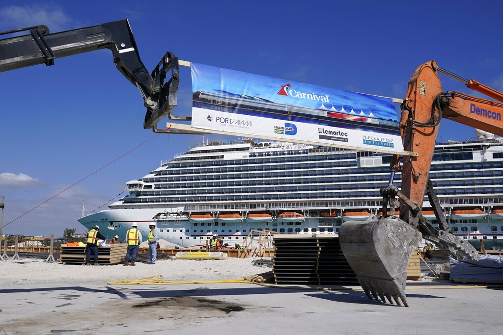 In this Friday, Jan. 29, 2021 photo, The Carnival Dream cruise ship arrives as construction work is underway for Carnival Cruise Line's new Terminal F, which will be the homeport to the Carnival Celebration cruise ship at PortMiami, in Miami. (AP Photo/Lynne Sladky)