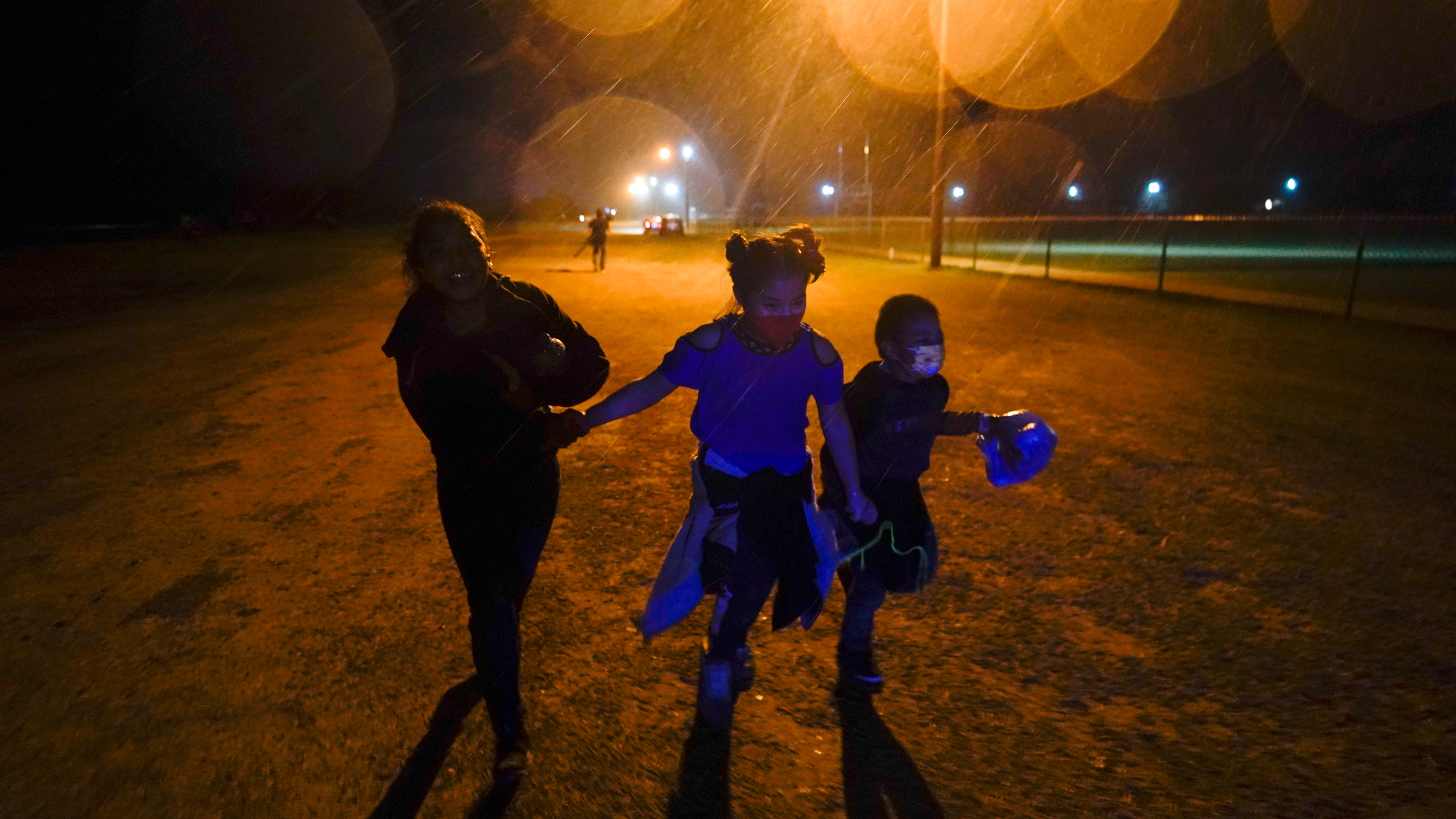 In this May 11, 2021, file photo, three young migrants hold hands as they run in the rain at an intake area after turning themselves in upon crossing the U.S.-Mexico border in Roma, Texas. Five months after the Biden administration declared an emergency and raced to set up shelters to house a record number of children crossing the U.S.-Mexico border alone, kids continue to languish at the sites, while more keep coming, child welfare advocates say. (AP Photo/Gregory Bull, File)