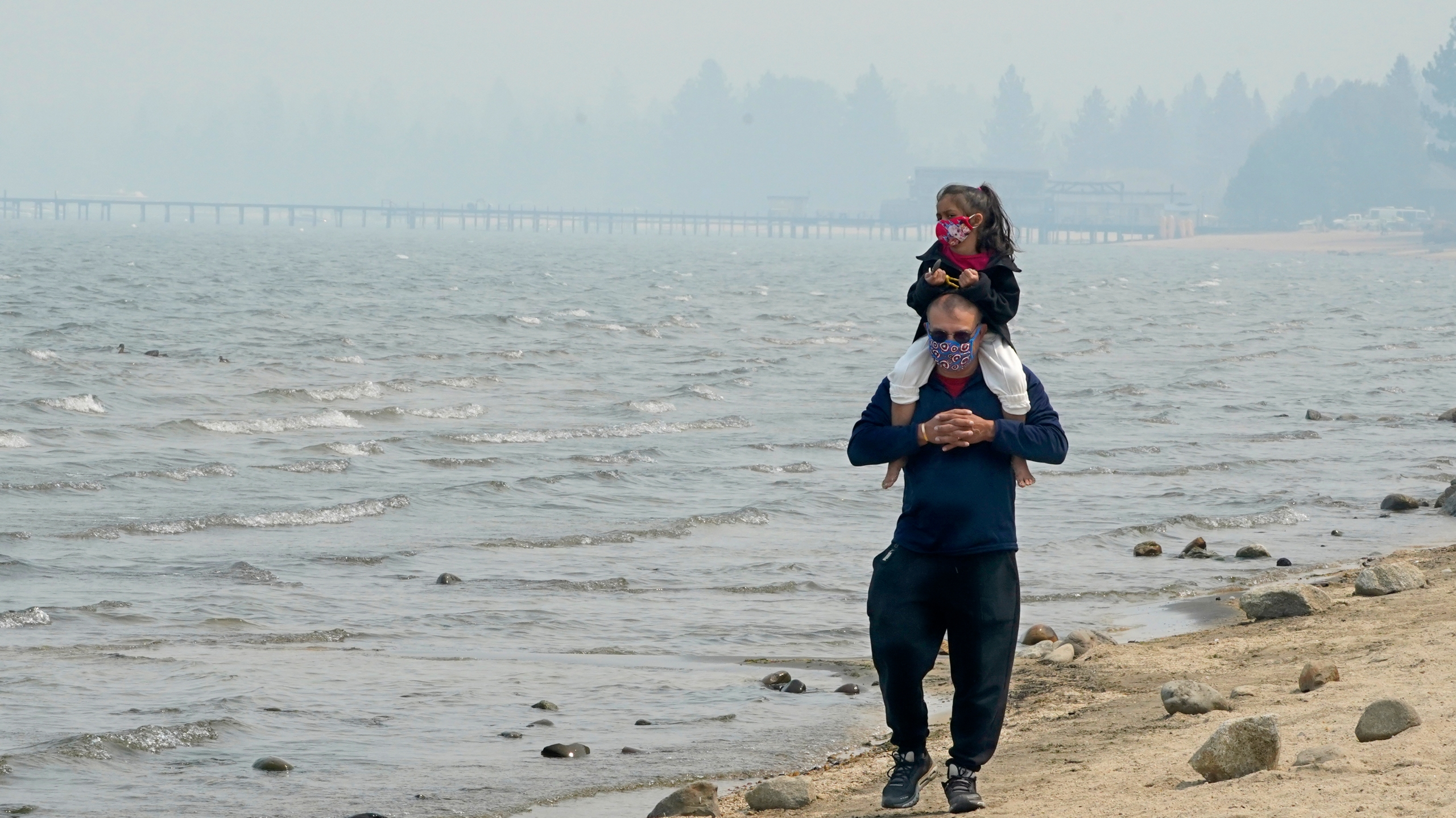 Presley Mila Perez gets a ride on the shoulders of George Estrada as they walk along the shore of Lake Tahoe in South Lake Tahoe on Aug. 24, 2021. (Rich Pedroncelli / Associated Press)