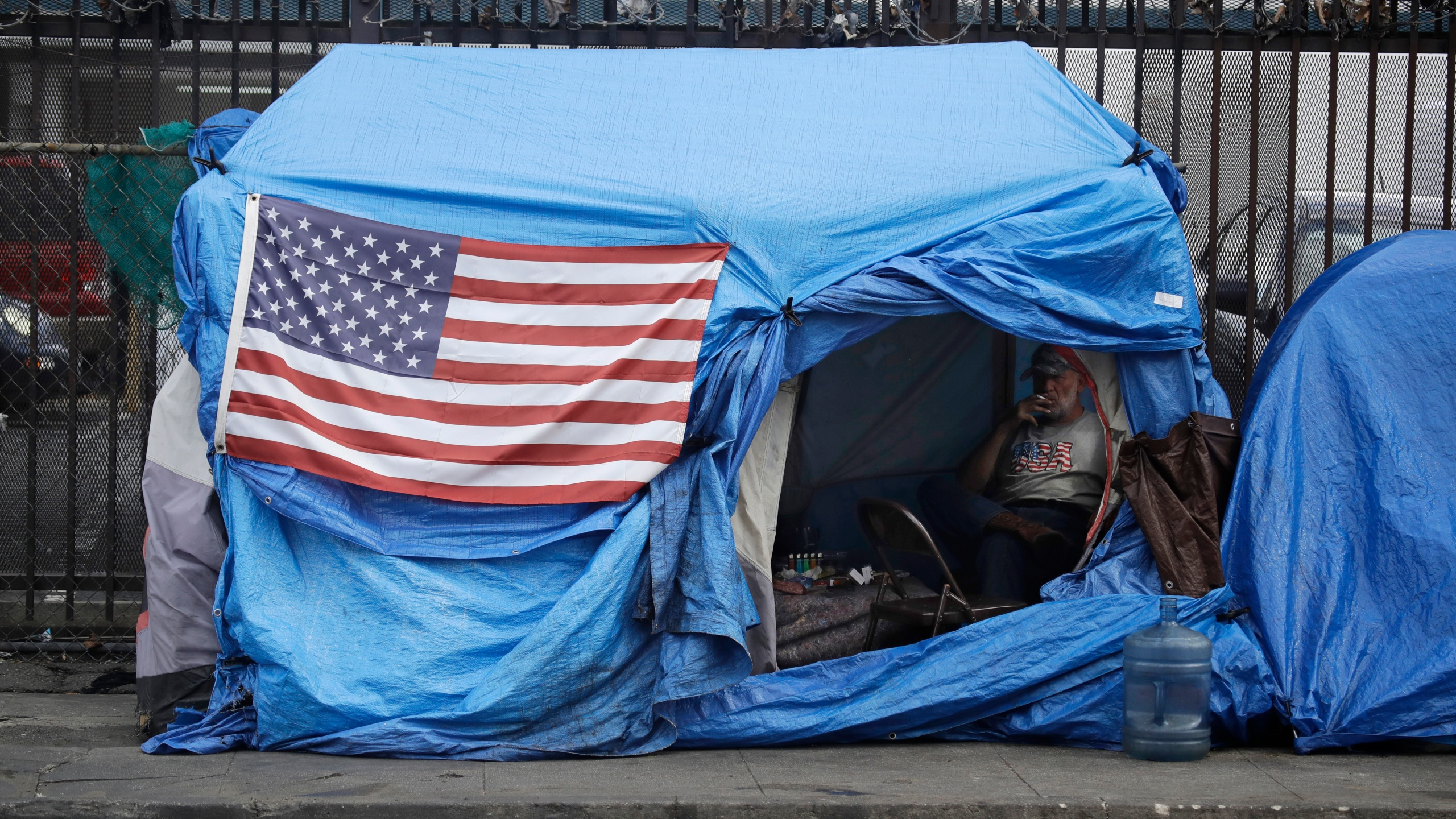 A man smokes inside a tent on skid row in Los Angeles on March 20, 2020. (Marcio Jose Sanchez / Associated Press)