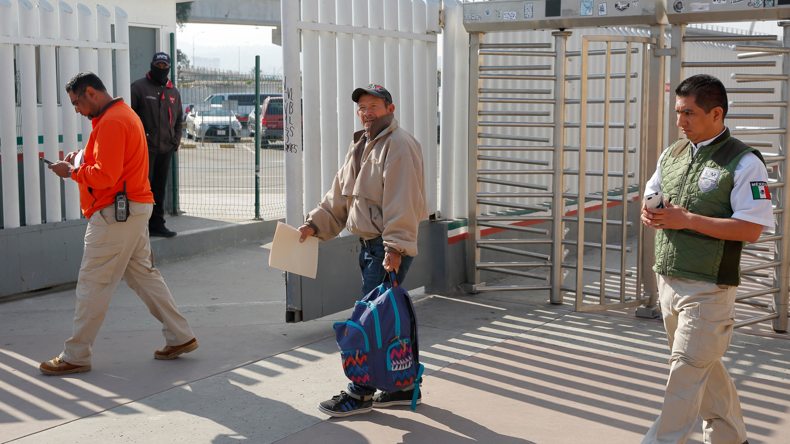 """In this Jan. 29, 2019, file photo, migrant Carlos Catarldo Gomez, of Honduras, center, is escorted by Mexican officials after leaving the U.S., the first person returned to Mexico to wait for his asylum trial date as part of a new program """"Remain In Mexico"""" policy in Tijuana, Mexico. The Supreme Court has ordered the reinstatement of the policy, saying that the Biden administration likely violated federal law by trying to end the Trump-era program that forces people to wait in Mexico while seeking asylum in the U.S. The decision immediately raised questions about what comes next for the future of the policy, also known as the Migrant Protection Protocols. (AP Photo/Gregory Bull, File)"""