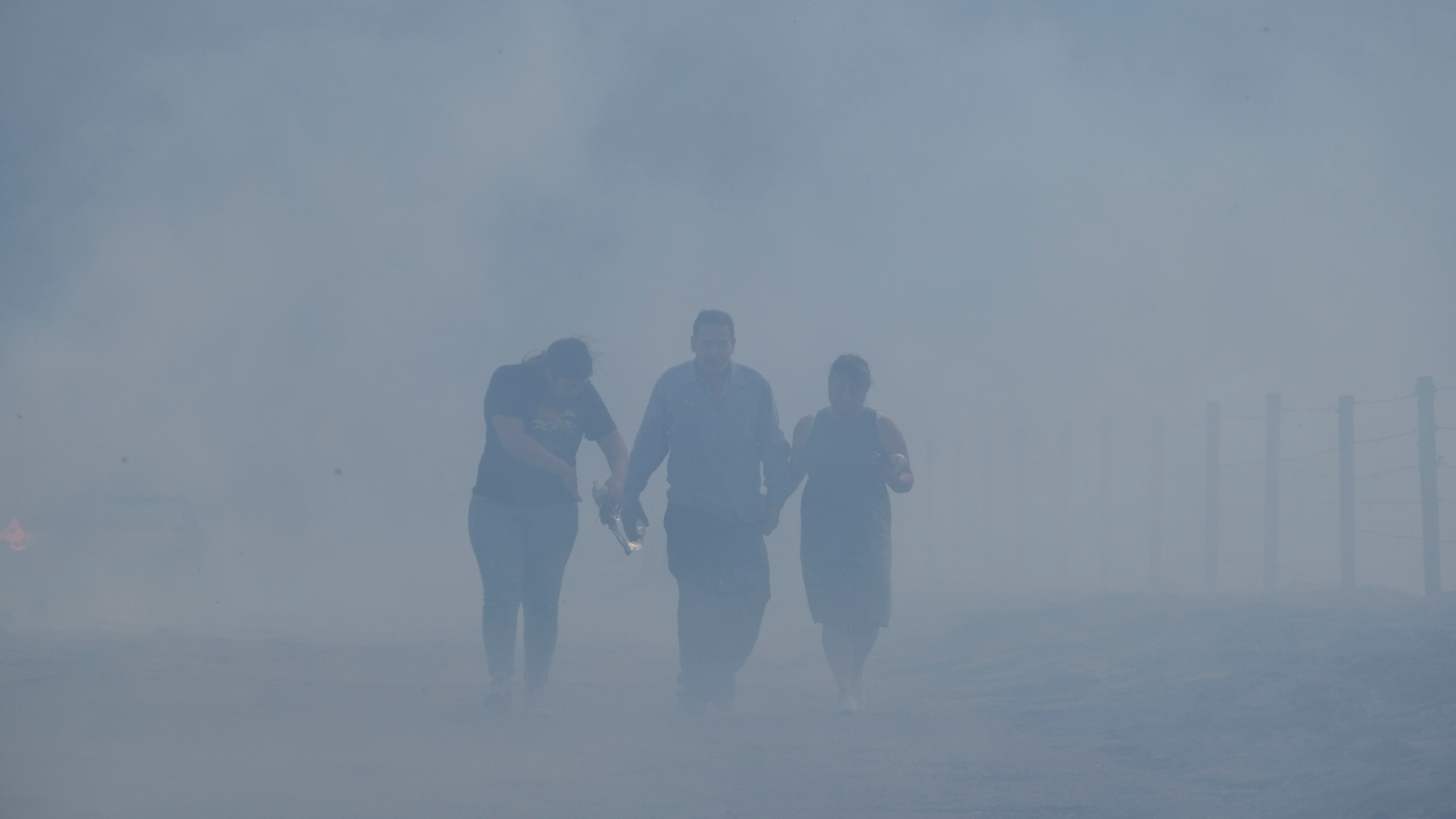 Homeowners Jose Lamas, center, his wife, Maria Covarrubias, right, and his daughter Astrid Covarrubias walk through the smoke after visiting their burned-out home from the South Fire in Lytle Creek, San Bernardino County, on Aug. 25, 2021. (Ringo H.W. Chiu / Associated Press)