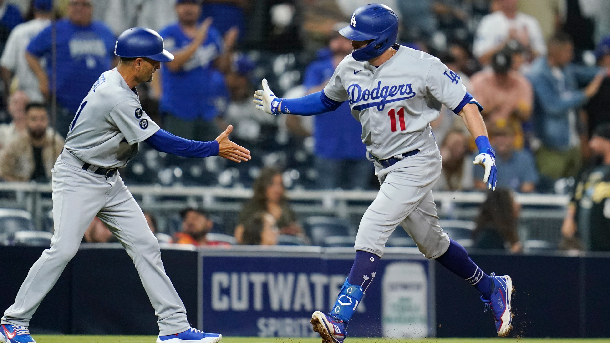 Los Angeles Dodgers' AJ Pollock, right, reacts with third base coach Dino Ebel after hitting a two-run home run during the 16th inning of a baseball game against the San Diego Padres on Aug. 26, 2021, in San Diego. (Gregory Bull/Associated Press)