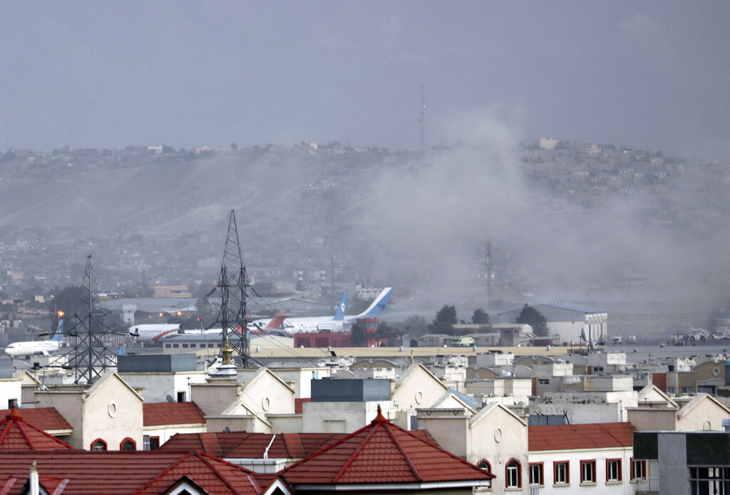 Smoke rises from explosion outside the airport in Kabul, Afghanistan on Aug. 26, 2021. The explosion went off outside Kabul's airport, where thousands of people have flocked as they try to flee the Taliban takeover of Afghanistan. (AP Photo/Wali Sabawoon)