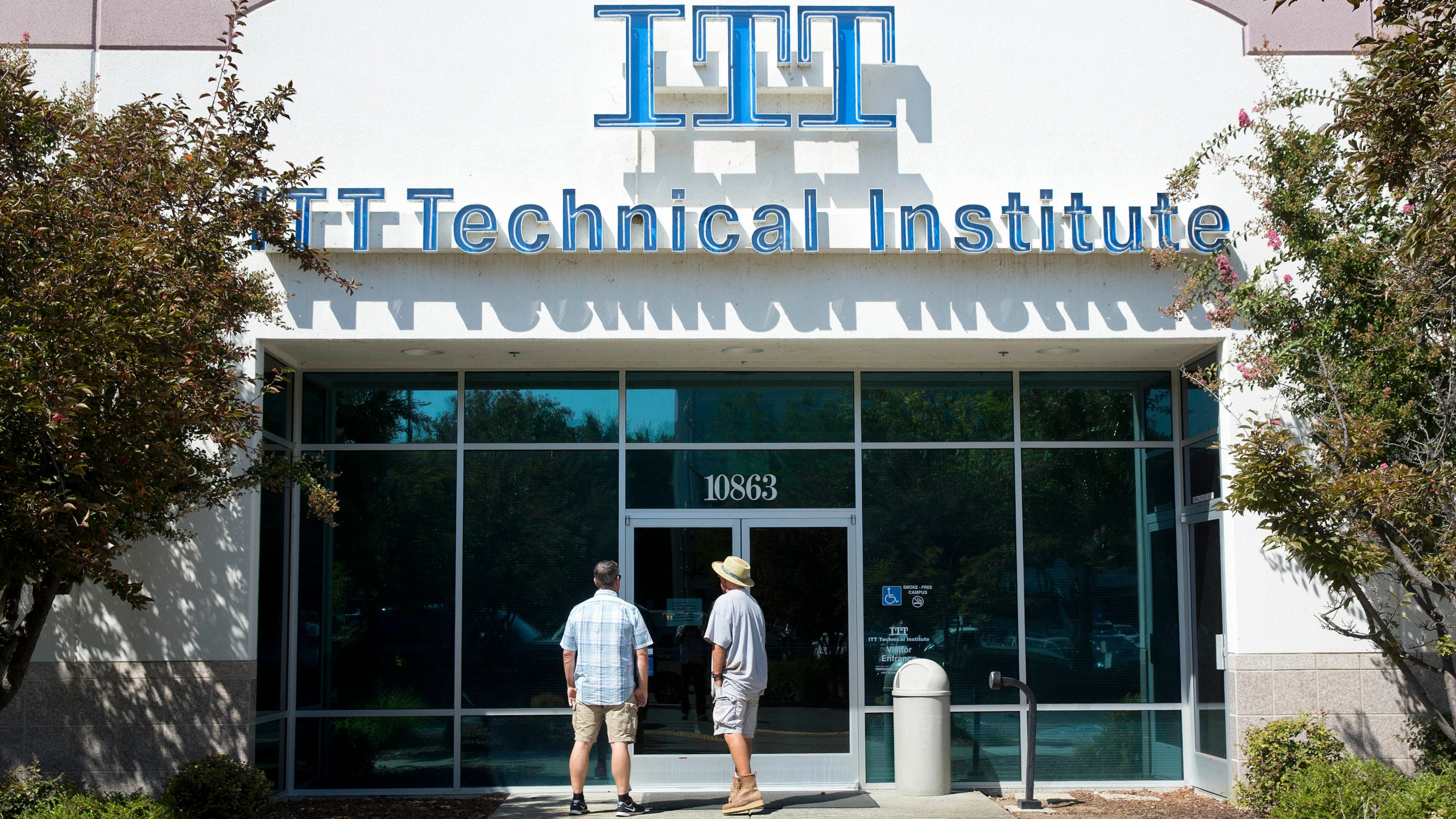 In this Sept. 6, 2016, file photo students find the doors locked to the ITT Technical Institute campus in Rancho Cordova, Calif. The U.S. Education Department announced Thursday, Aug. 26, 2021, it will forgive student debt for more than 100,000 borrowers who attended the now-defunct ITT Technical Institute chain but left before graduating. (AP Photo/Rich Pedroncelli, File)
