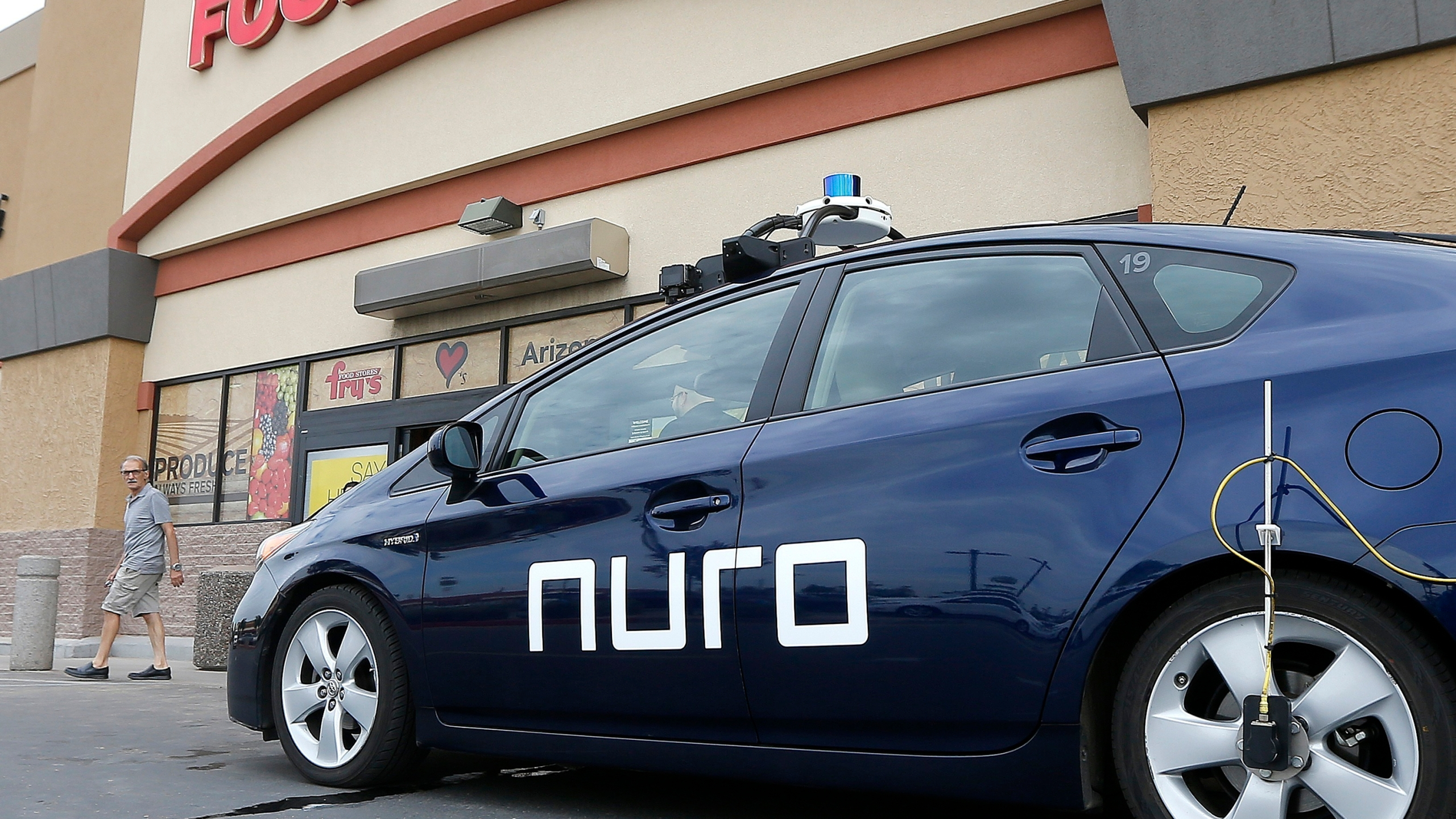 In this Aug. 16, 2018, file photo, a self-driving Nuro vehicle parks outside a Fry's supermarket, which is owned by Kroger, as part of a pilot program for grocery deliveries in Scottsdale, Ariz. Nuro, the robotics company that develops driverless vehicles for on-road grocery, pizza and prescription deliveries said Thursday, Aug. 26, 2021, it intends to spend $40 million to put a manufacturing facility at the Las Vegas Motor Speedway. (AP Photo/Ross D. Franklin, File)