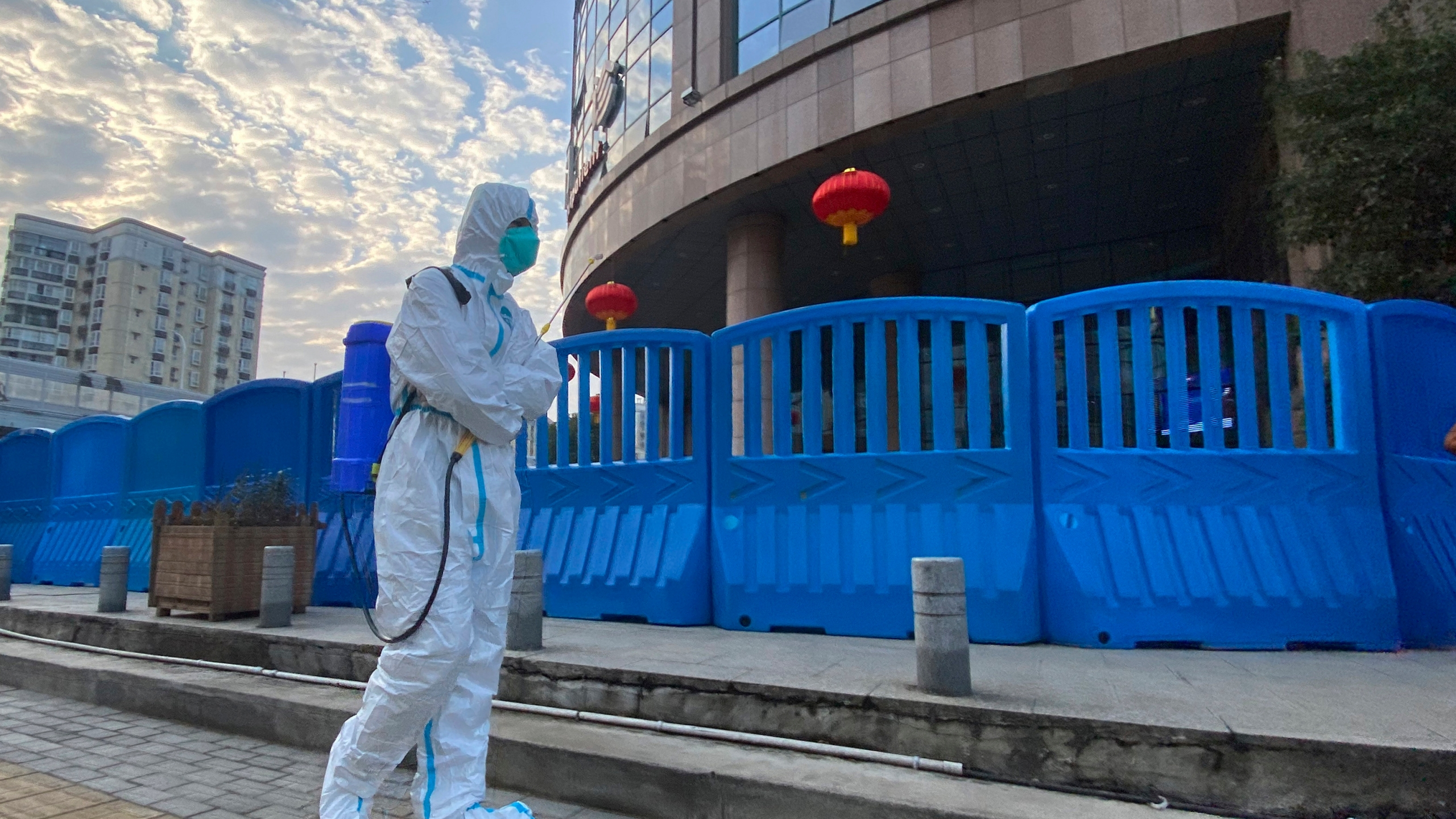 In this Feb. 6, 2021, file a worker in protectively overalls and carrying disinfecting equipment walks outside the Wuhan Central Hospital where Li Wenliang, the whistleblower doctor who sounded the alarm and was reprimanded by local police for it in the early days of Wuhan's pandemic, worked in Wuhan in central China. U.S. intelligence agencies remain divided on the origins of the coronavirus but believe China's leaders did not know about the virus before the start of the global pandemic, according to results released Friday, Aug. 27, of a review ordered by President Joe Biden. (AP Photo/Ng Han Guan, File)
