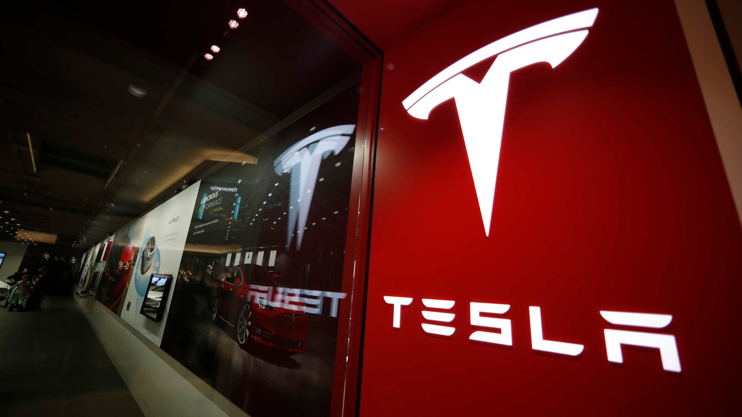This Feb. 9, 2019, file photo shows a sign bearing the company logo outside a Tesla store in Cherry Creek Mall in Denver. A Tesla using its partially automated driving system slammed into a Florida Highway Patrol cruiser Saturday, Aug. 28, 2021 on an interstate near downtown Orlando and narrowly missed its driver, who had pulled over to assist a disabled vehicle. (AP Photo/David Zalubowski, File)