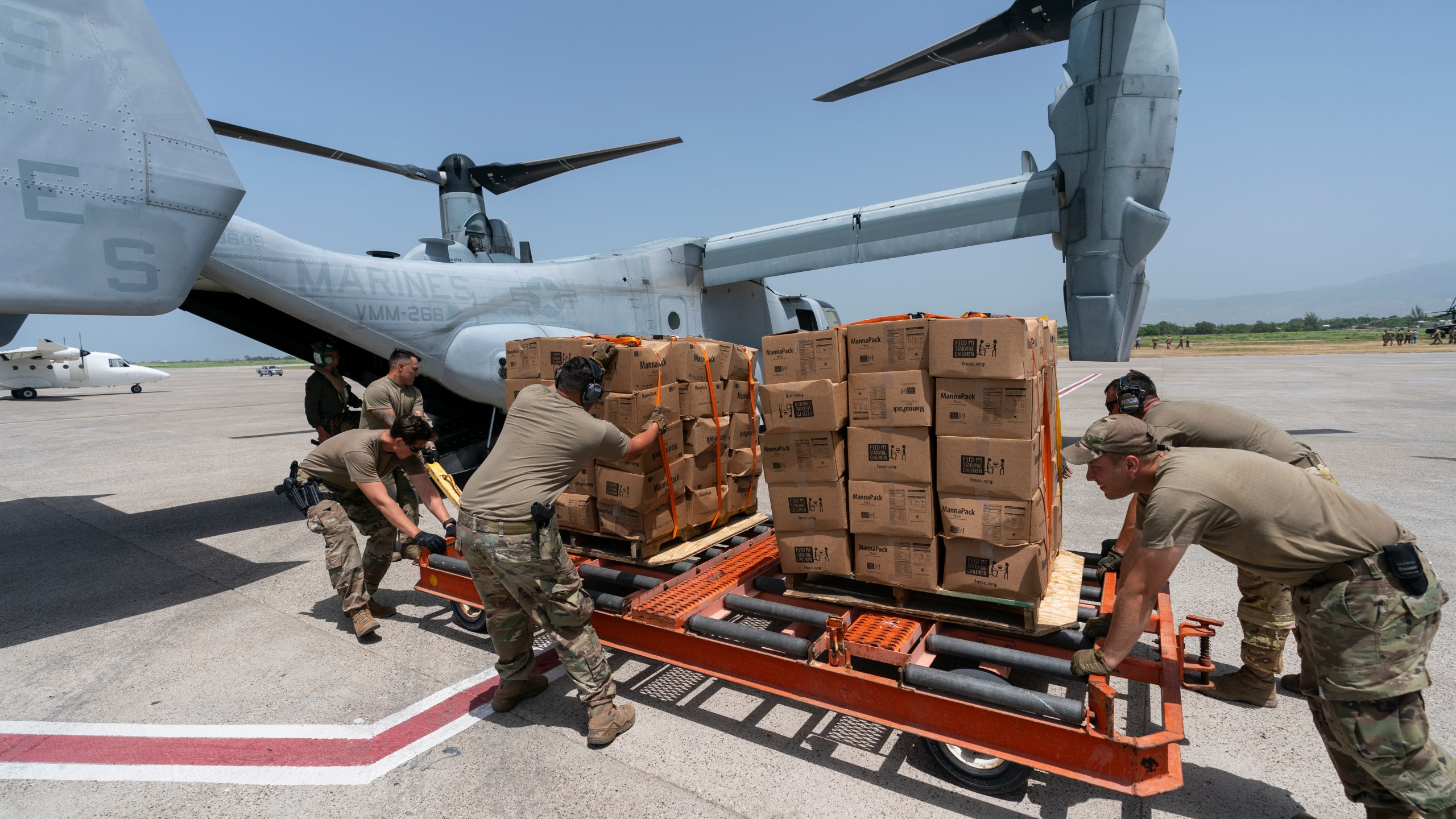 """Food is loaded onto a VM-22 Osprey at Toussaint Louverture International Airport, Saturday, Aug. 28, 2021, in Port-au-Prince, Haiti. The VMM-266, """"Fighting Griffins,"""" from Marine Corps Air Station New River, from Jacksonville, N.C., are flying in support of Joint Task Force Haiti after a 7.2 magnitude earthquake on Aug. 22, caused heavy damage to the country. (AP Photo/Alex Brandon)"""