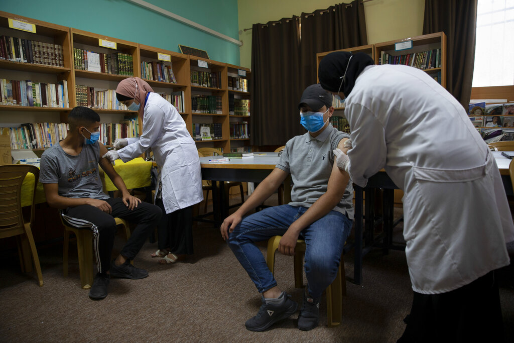 Health workers administer Moderna COVID-19 vaccines to Palestinian students during a back to school vaccination campaign, in the West Bank city of Ramallah, Monday, Aug. 30, 2021. (AP Photo/Majdi Mohammed)