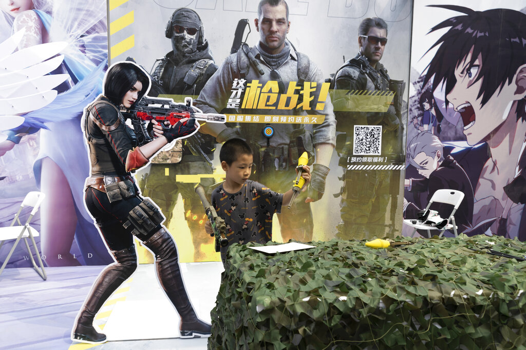 A child plays with a toy gun during a promotion for online games in Beijing on Saturday, Aug. 29, 2020. (AP Photo/Ng Han Guan)