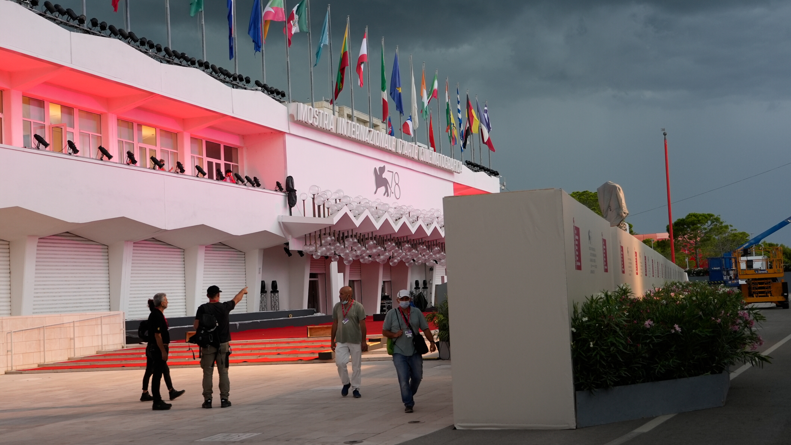 Workers walk by a wall hiding the red carpet of the 78th edition of the Venice Film Festival from the view of the public at the Venice Lido, Italy on Aug. 30, 2021. (Domenico Stinellis/Associated Press)