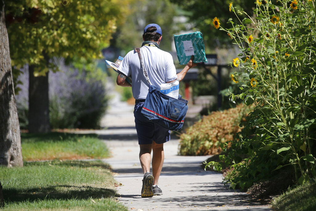 In this Aug. 17, 2020, file photo, a United States Postal Service carrier delivers mail to homes in Salt Lake City. (AP Photo/Rick Bowmer, File)