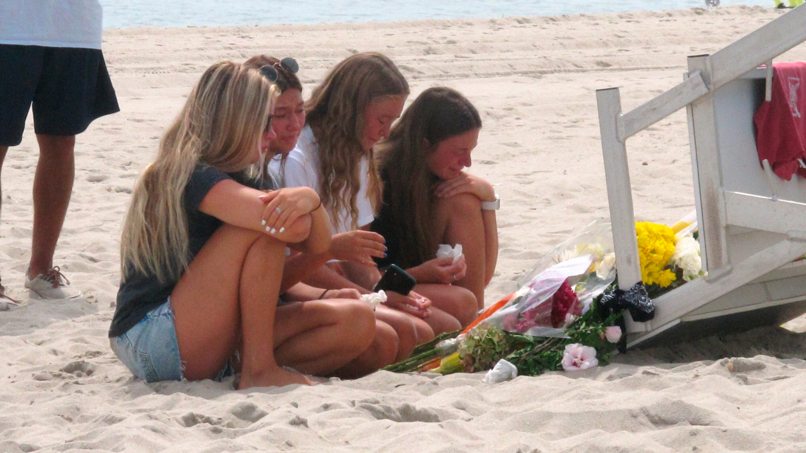 Friends and fellow lifeguards cry at the foot of a lifeguard stand in Berkeley Township, N.J., on Aug. 31, 2021, a day after 19-year-old lifeguard Keith Pinto was killed by lightning there. (Wayne Parry / Associated Press)