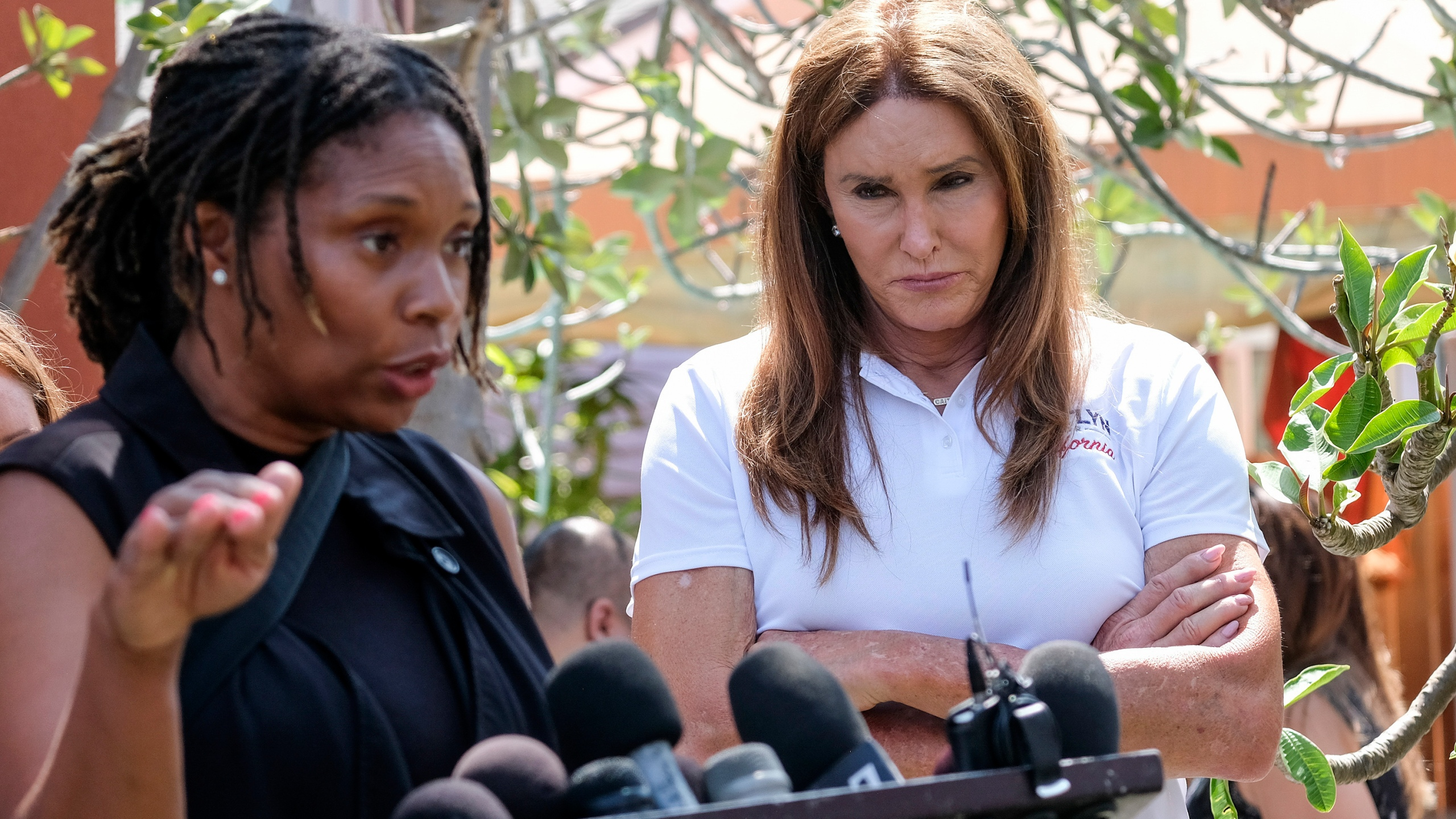 Caitlyn Jenner, right, a Republican candidate for California governor, looks on as Chie Lunn speaks during a news conference in the Venice Beach section of Los Angeles, Aug. 12, 2021. (AP Photo/Ringo H.W. Chiu)