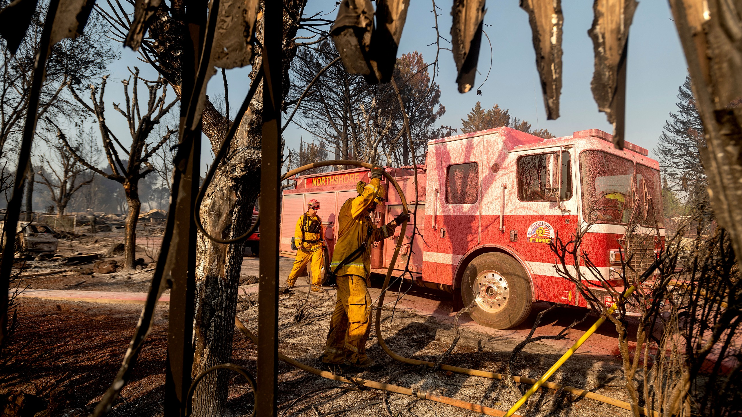 Firefighters mop up at Cache Creek Mobile Home Estates where the Cache Fire leveled dozens of residences on Wednesday, Aug. 18, 2021, in Clearlake, Calif. (AP Photo/Noah Berger)