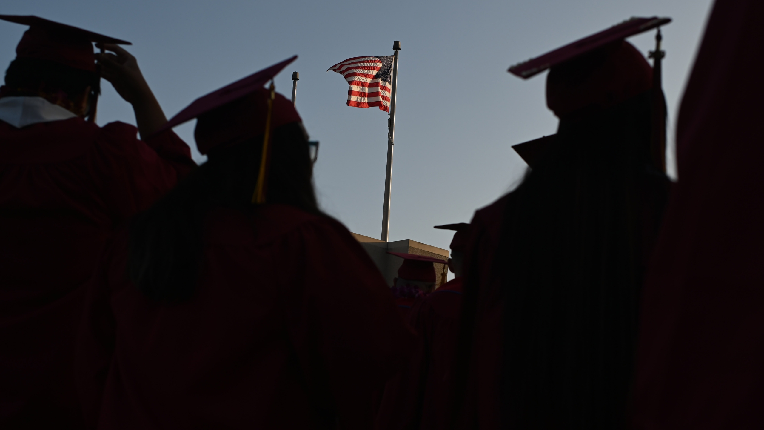 A U.S. flag flies above a building at a Pasadena City College graduation ceremony on June 14, 2019, in Pasadena. (ROBYN BECK/AFP via Getty Images)
