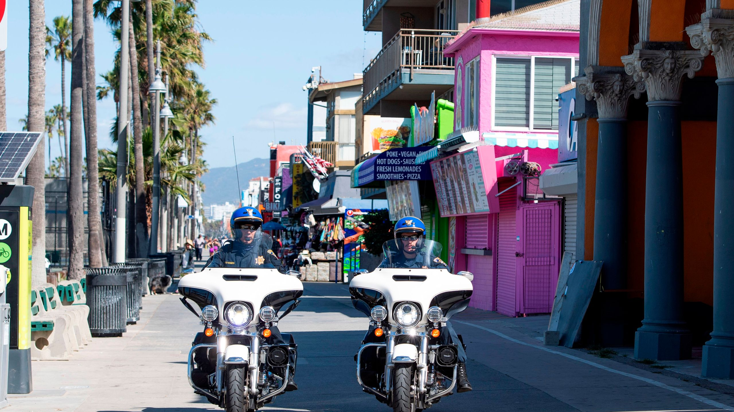 This file photo shows police officers patrolling the boardwalk in Venice Beach on May 13, 2020.(VALERIE MACON/AFP via Getty Images)
