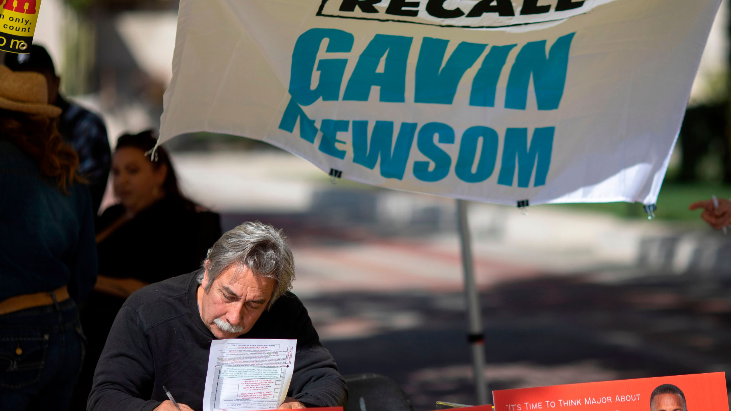 Paul Von Lutzow signs a petition as conservative activists gather signatures in a recall effort against California Governor Gavin Newsom near Pasadena City Hall, in Pasadena, California on February 28, 2021. (DAVID MCNEW/AFP via Getty Images)