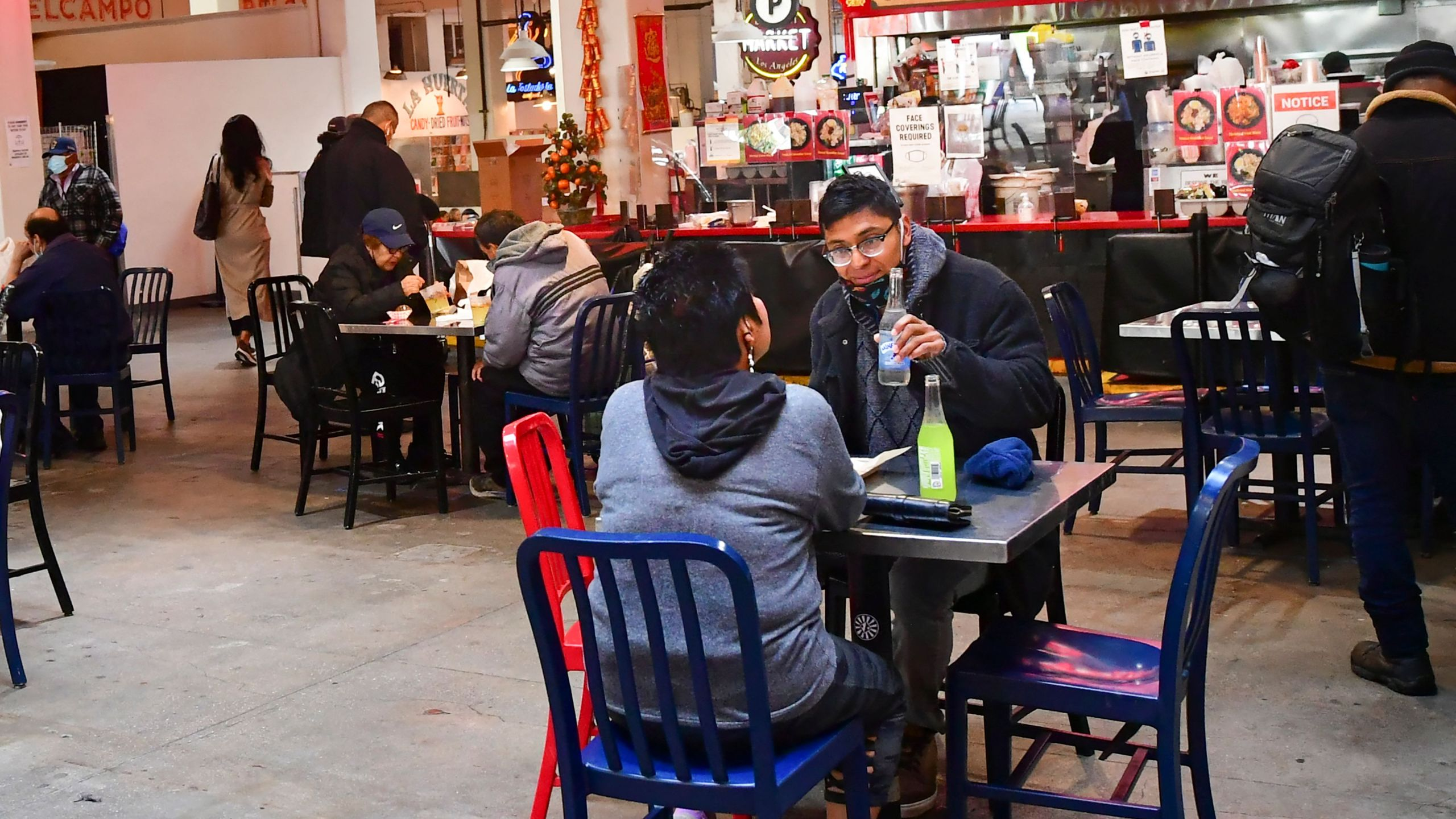 People enjoy lunch at Grand Central Market as indoor dining reopens in Los Angeles, on March 15, 2021. (FREDERIC J. BROWN/AFP via Getty Images)