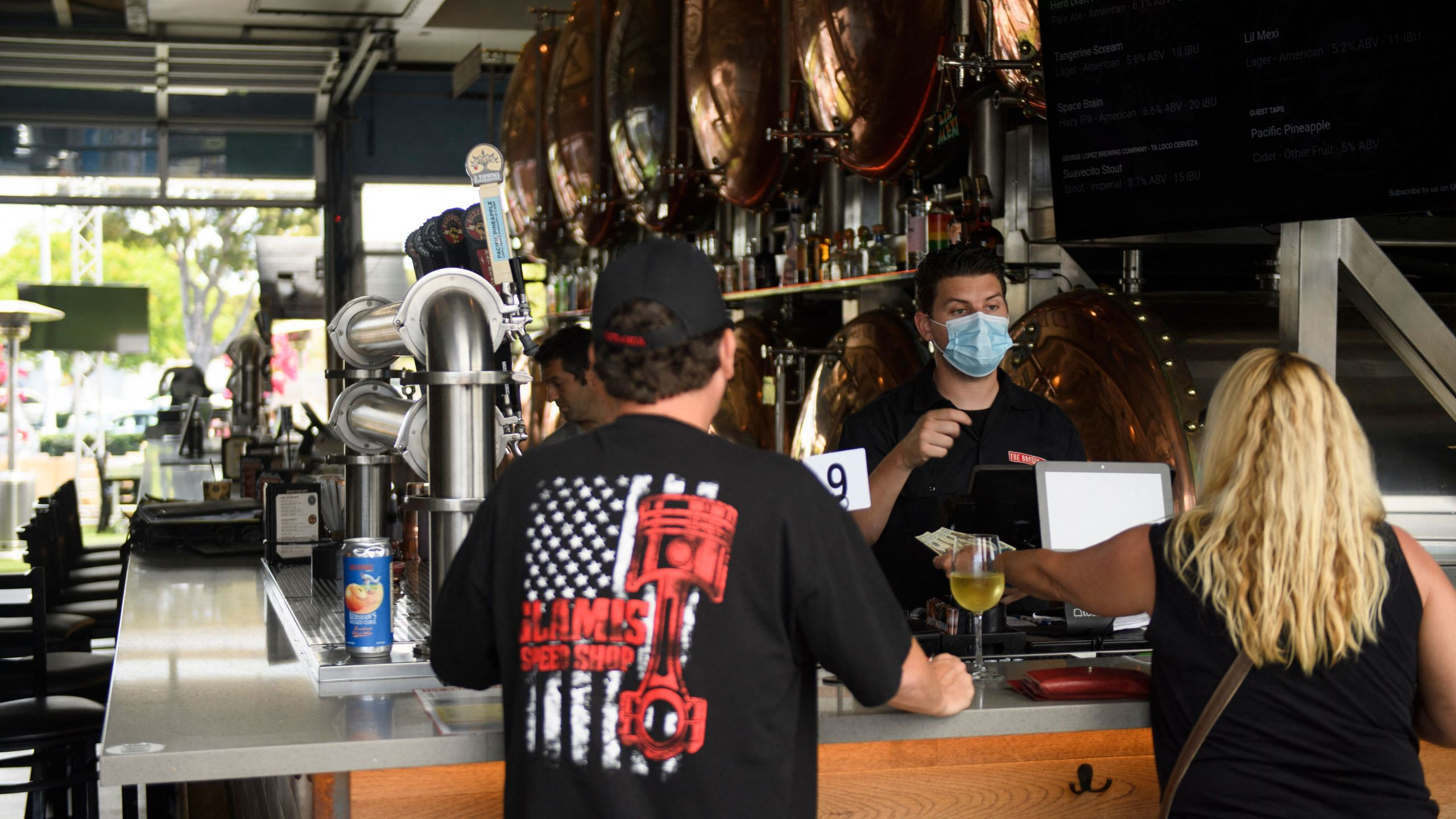 A bartender assists customers with a purchase at The Brew Hall on June 23, 2021 in Torrance, California. (PATRICK T. FALLON/AFP via Getty Images)
