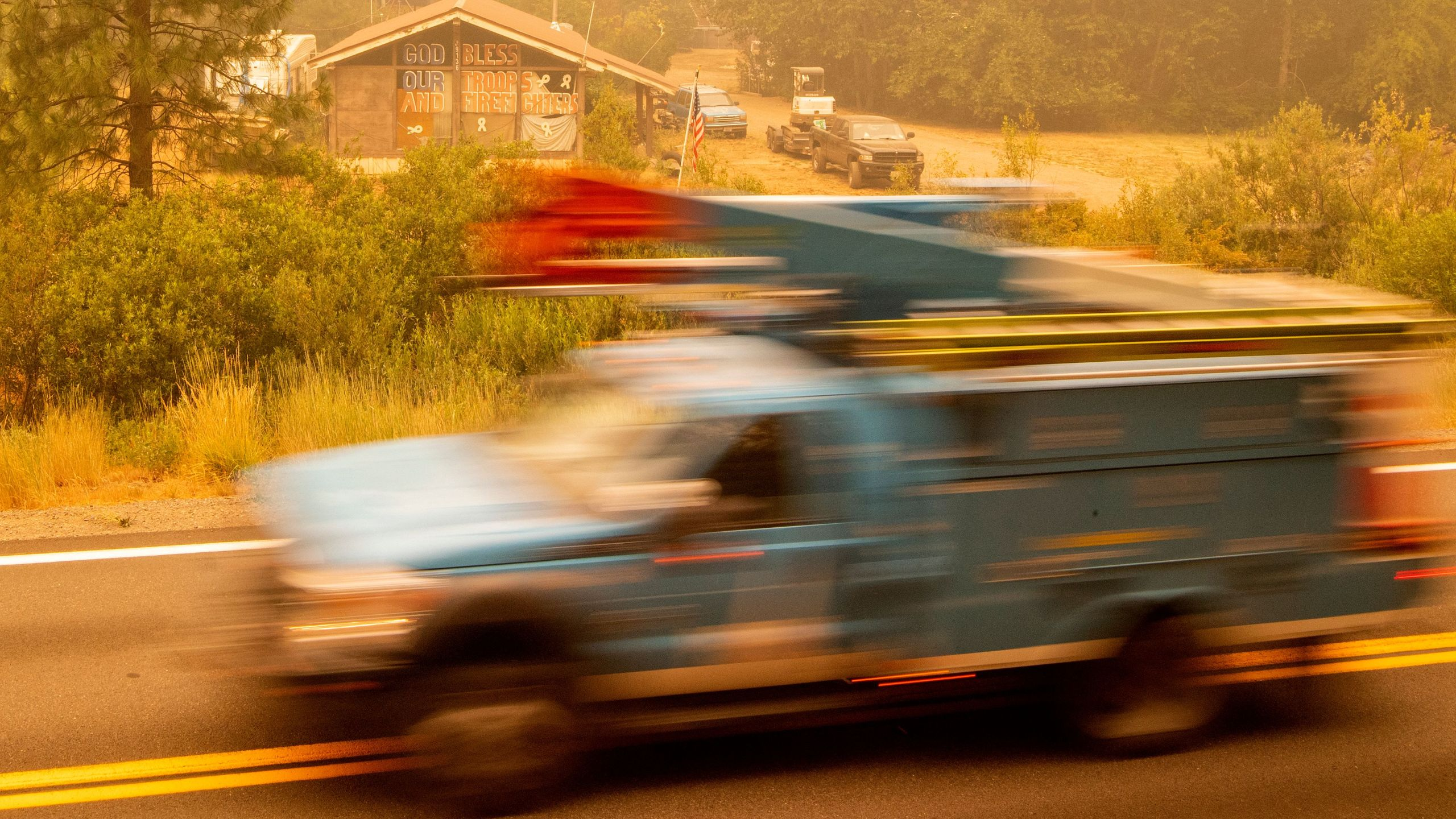 A PG&E truck passes by a home with a message to firefighters during the Dixie Fire near Quincy on July 26, 2021. (JOSH EDELSON/AFP via Getty Images)