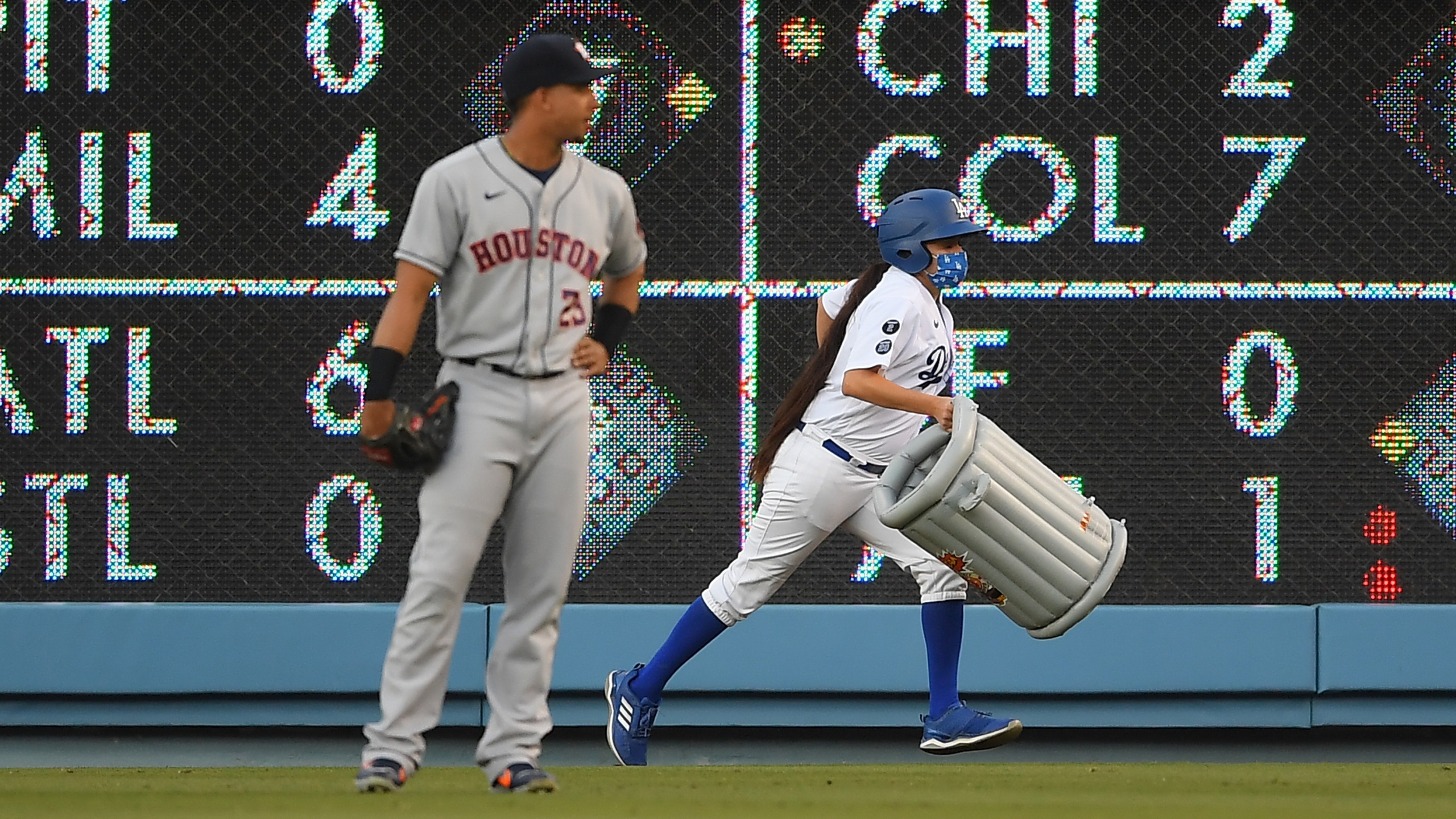 Michael Brantley #23 of the Houston Astros watches as a bat girl removes an inflatable trash can that was thrown onto the field in the first inning against the Los Angeles Dodgers at Dodger Stadium on Aug. 3, 2021, in Los Angeles, California. (Jayne Kamin-Oncea/Getty Images)