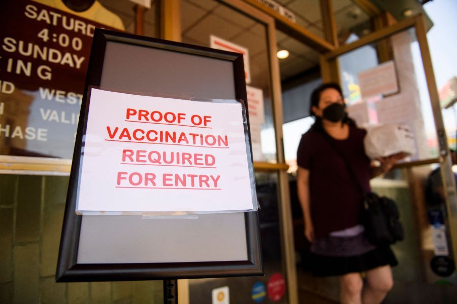A sign saying that proof of COVID-19 vaccination is required is displayed outside of Langer's Deli in Los Angeles on Aug. 7, 2021. (PATRICK T. FALLON/AFP via Getty Images)