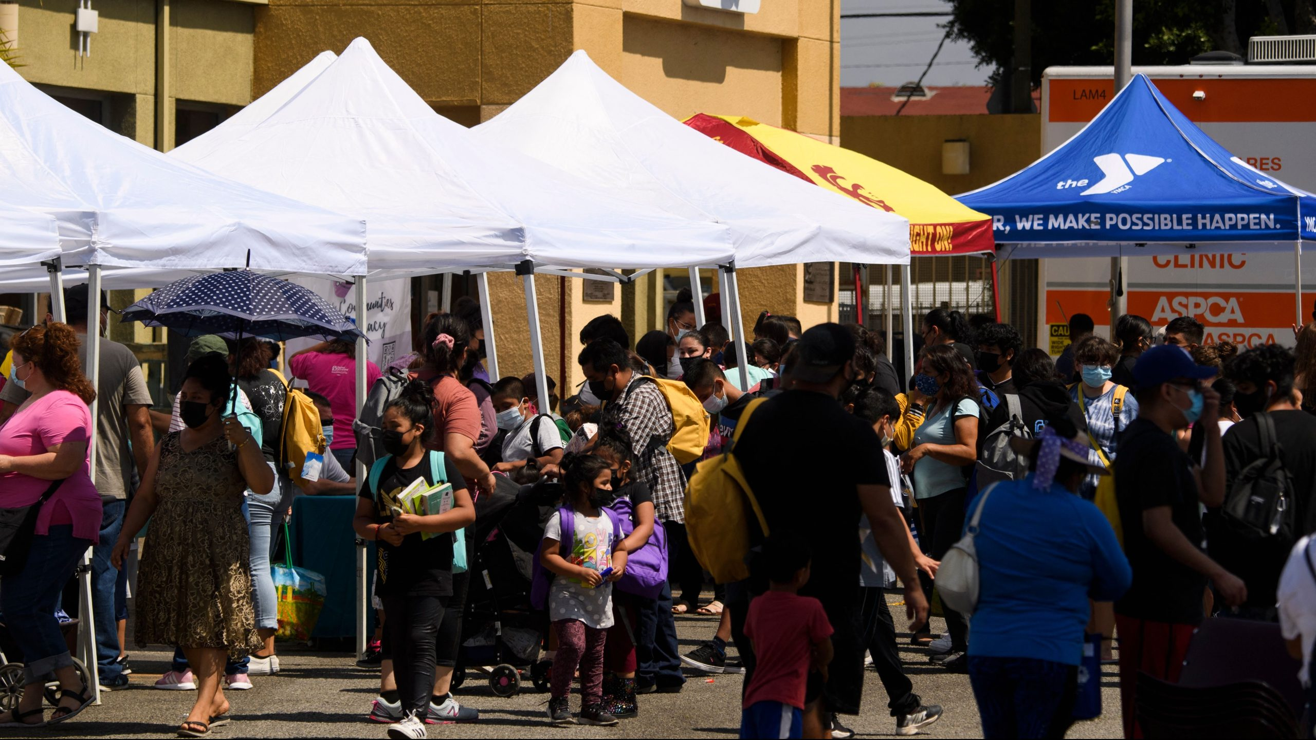 Families attend a back to school event offering school supplies, COVID-19 vaccinations, face masks and other resources for children and their families at the Weingart East Los Angeles YMCA on Aug. 7, 2021. (Patrick T. Fallon / AFP / Getty Images)