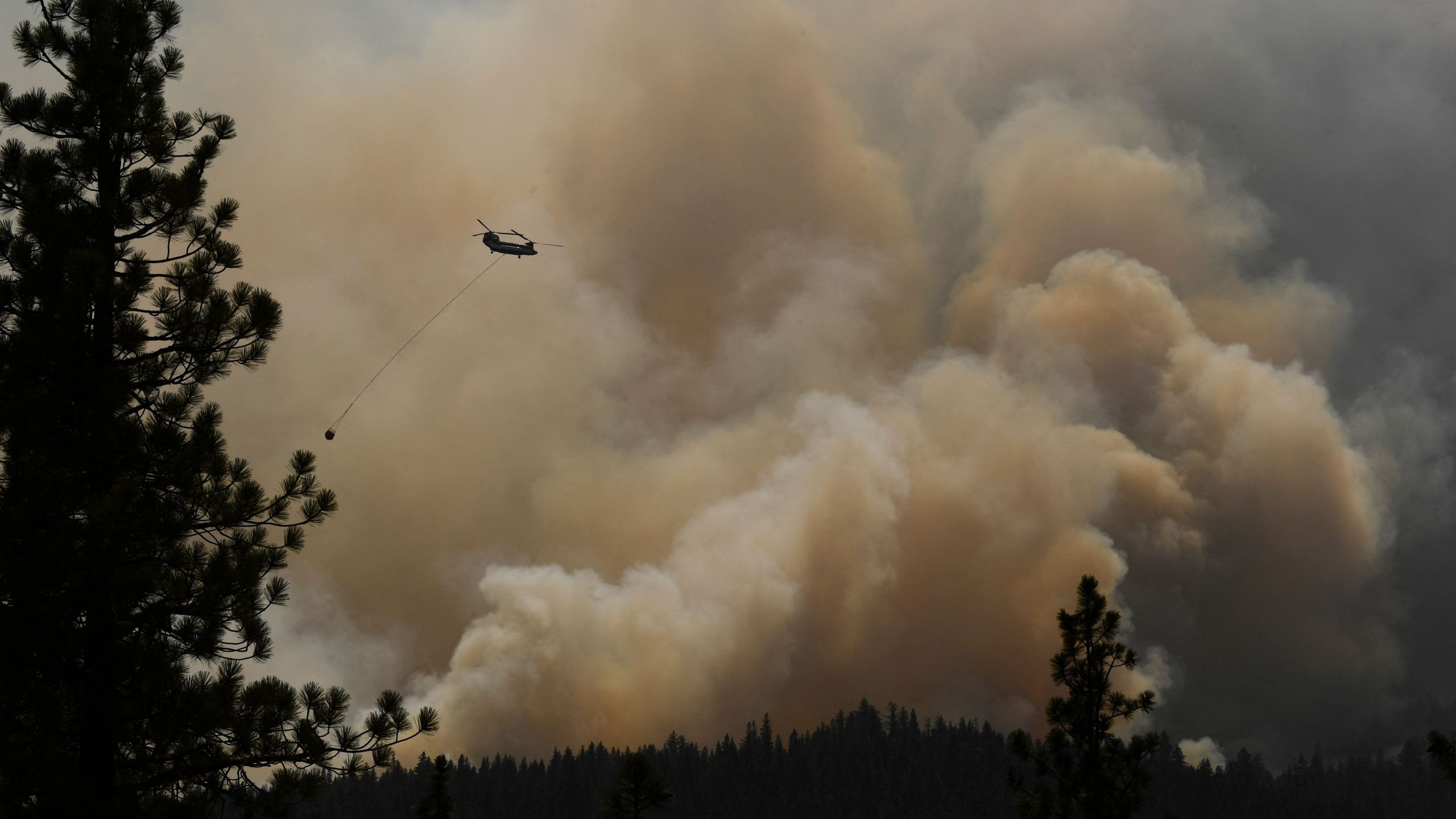 A firefighting helicopter flies past smoke plumes after making a water drop during the Dixie Fire on Aug. 18, 2021 near Susanville, California. (PATRICK T. FALLON/AFP via Getty Images)