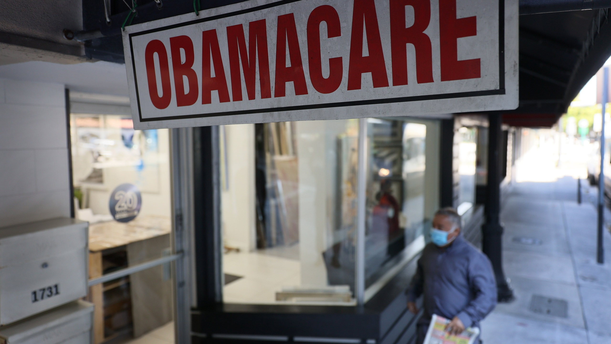 A pedestrian walks past an insurance agency offering plans under the Affordable Care Act on Jan. 28, 2021 in Miami, Florida. (Joe Raedle/Getty Images)